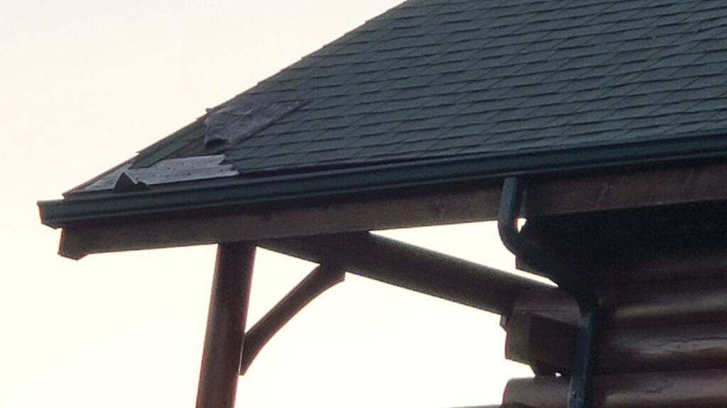 This is a picture taken from the ground of a green shingles roof that has a section of missing shingles on the back left corner of the roof
