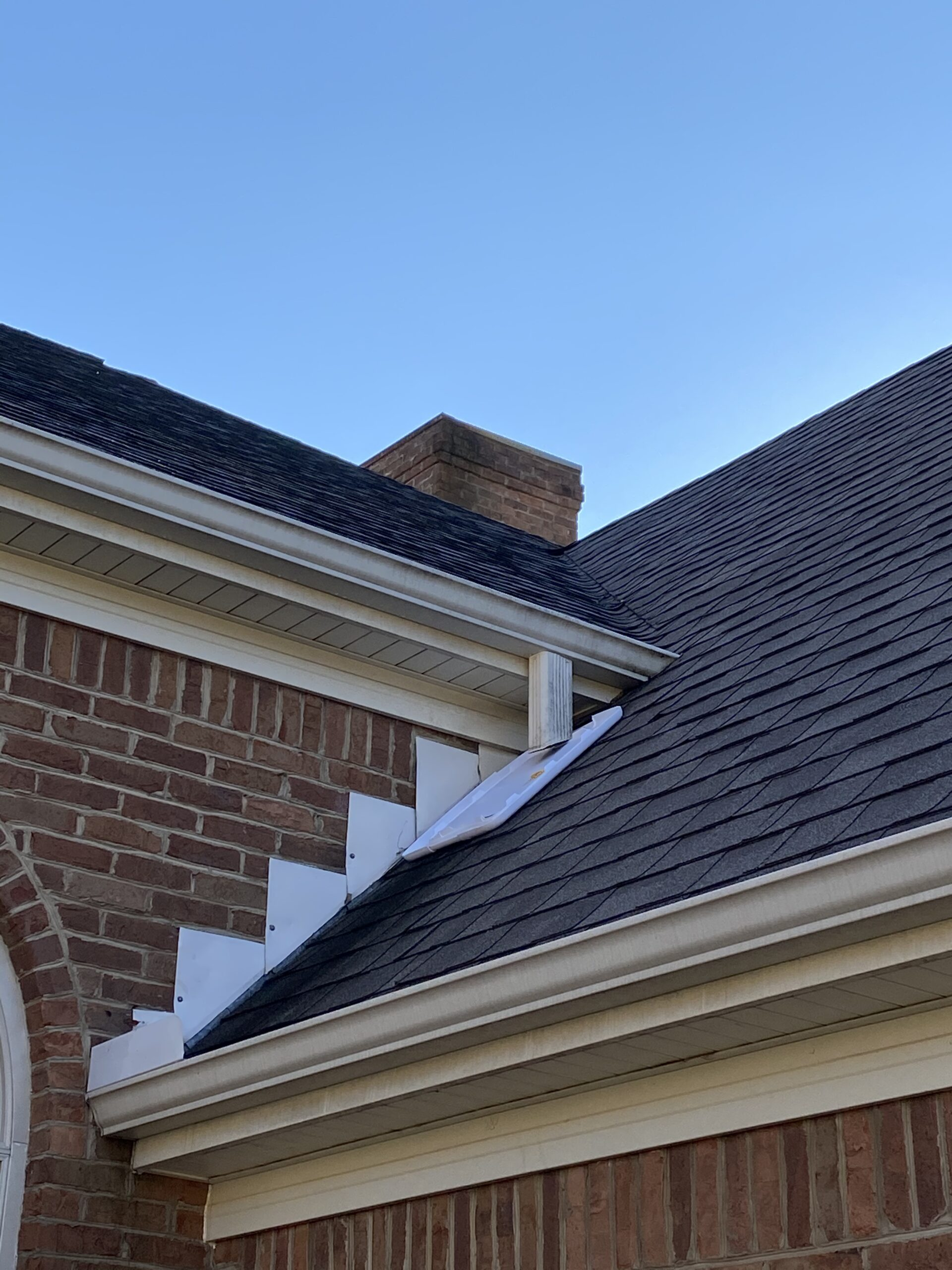 The a picture of a gutter that buts up against the roof possibly causing overflow