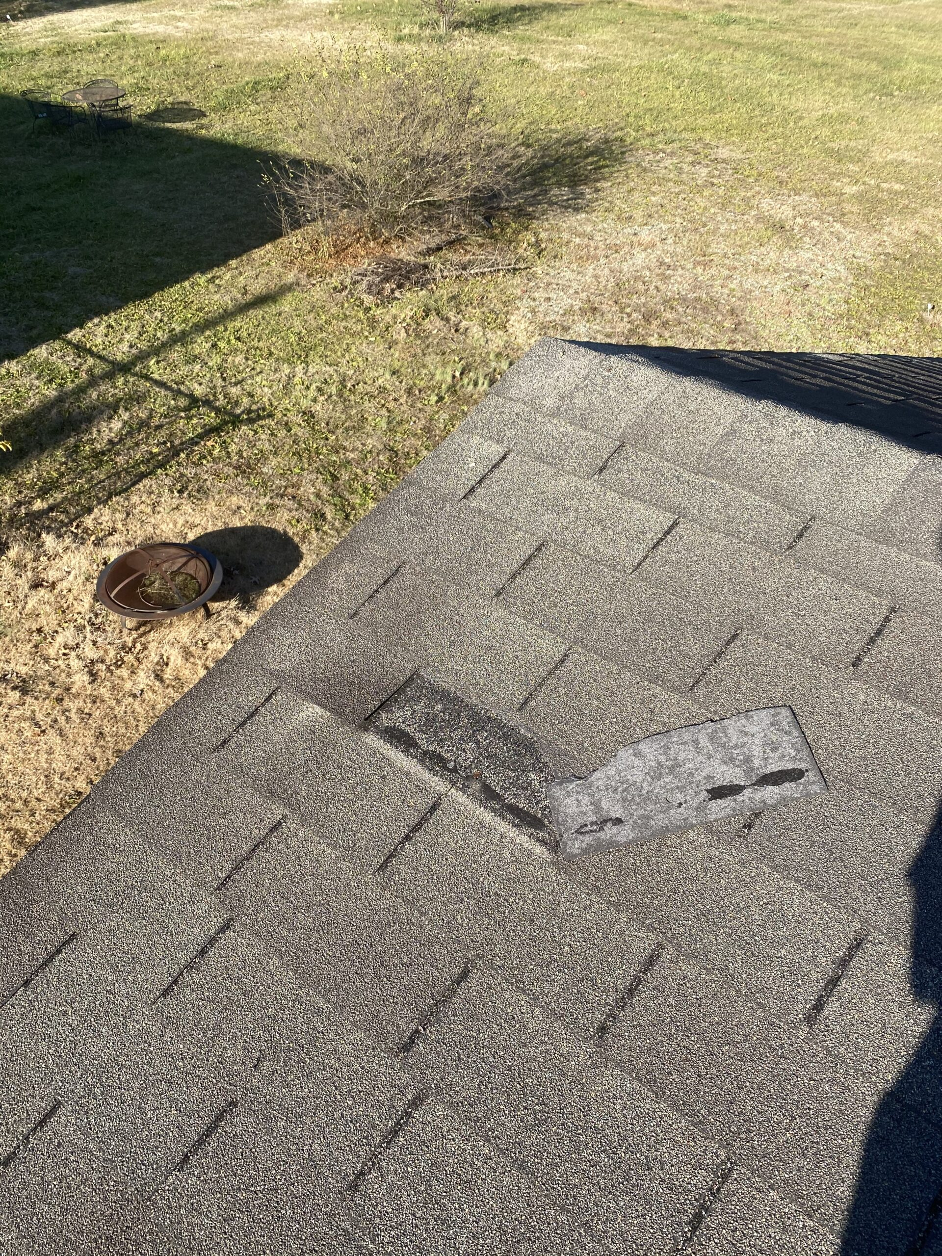 This is a picture of an old 3 tab shingle that has wind damage.