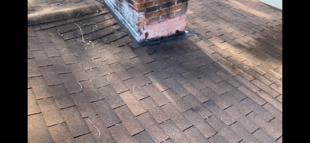 The low slope area on this three tab shingle roof does not appear to be having trouble, however the flashing around the chimney is causing some problems in this area