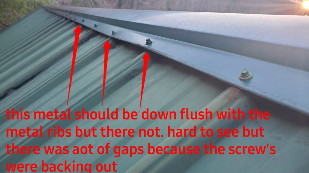 This is a picture of the ridge of a metal roof with red arrows on it