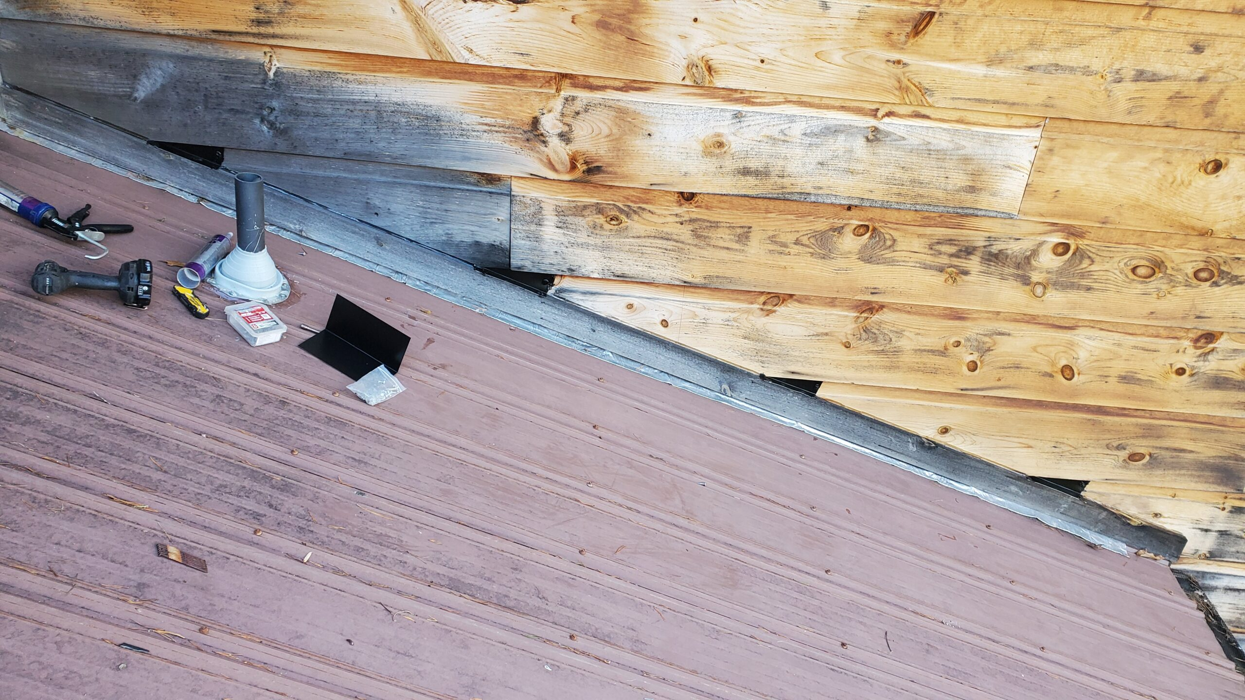 This is a picture of a wall with wooden siding that has triangular pieces of metal flashing between each piece of siding. Closing the gaps between each siding piece