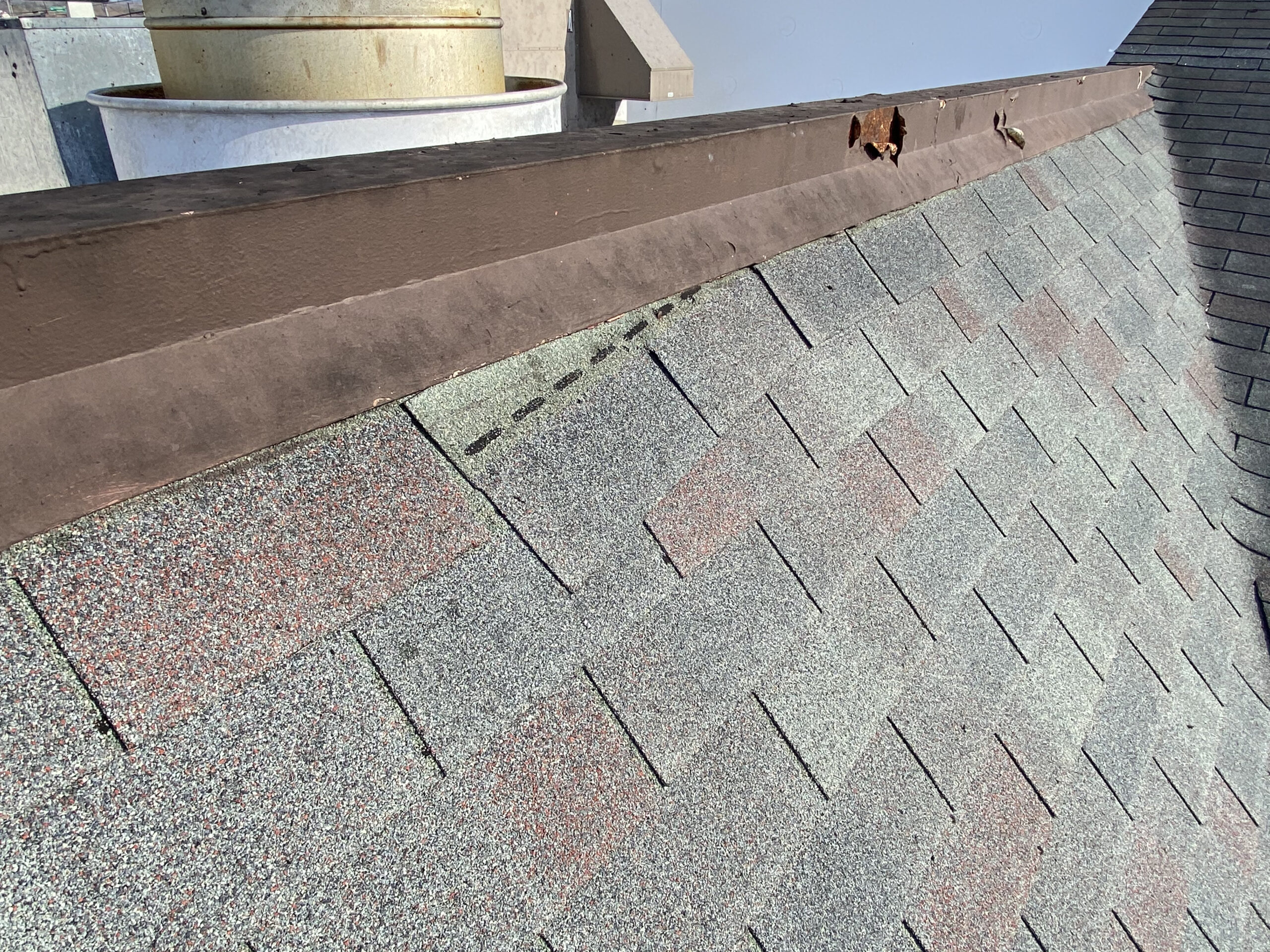 This is a picture of an old green three tab roof on a brown building