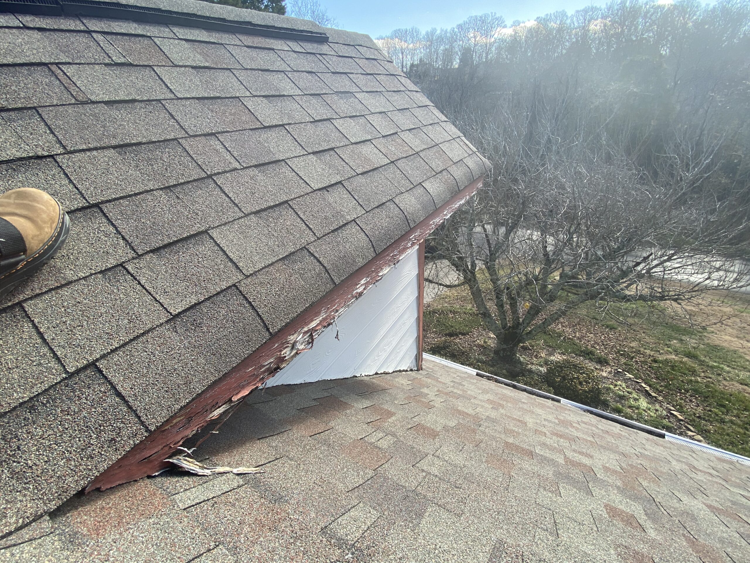 This is a picture of a white and red dormer with rotting fascia boards