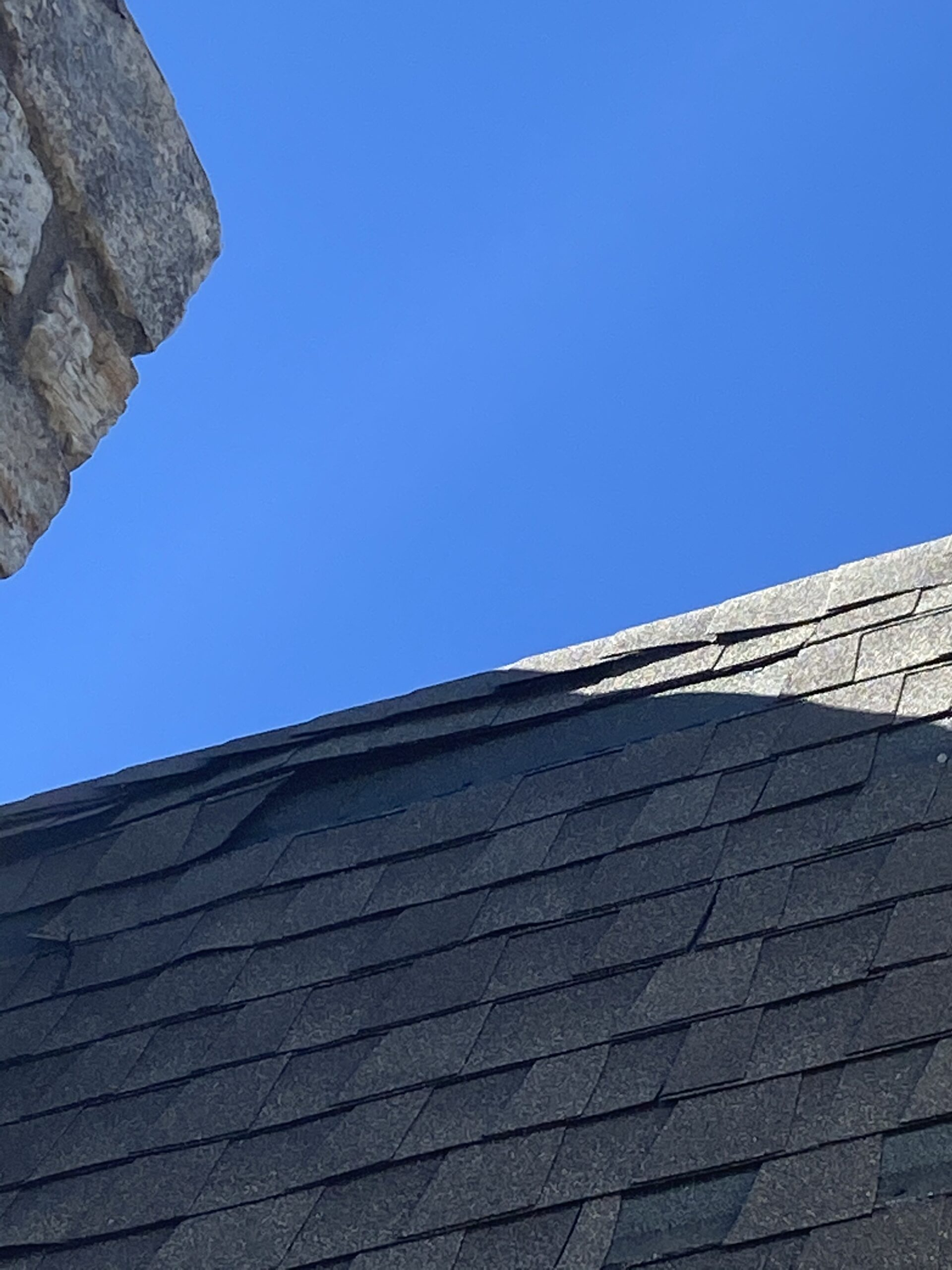 This is a picture of missing shingles behind the chimney