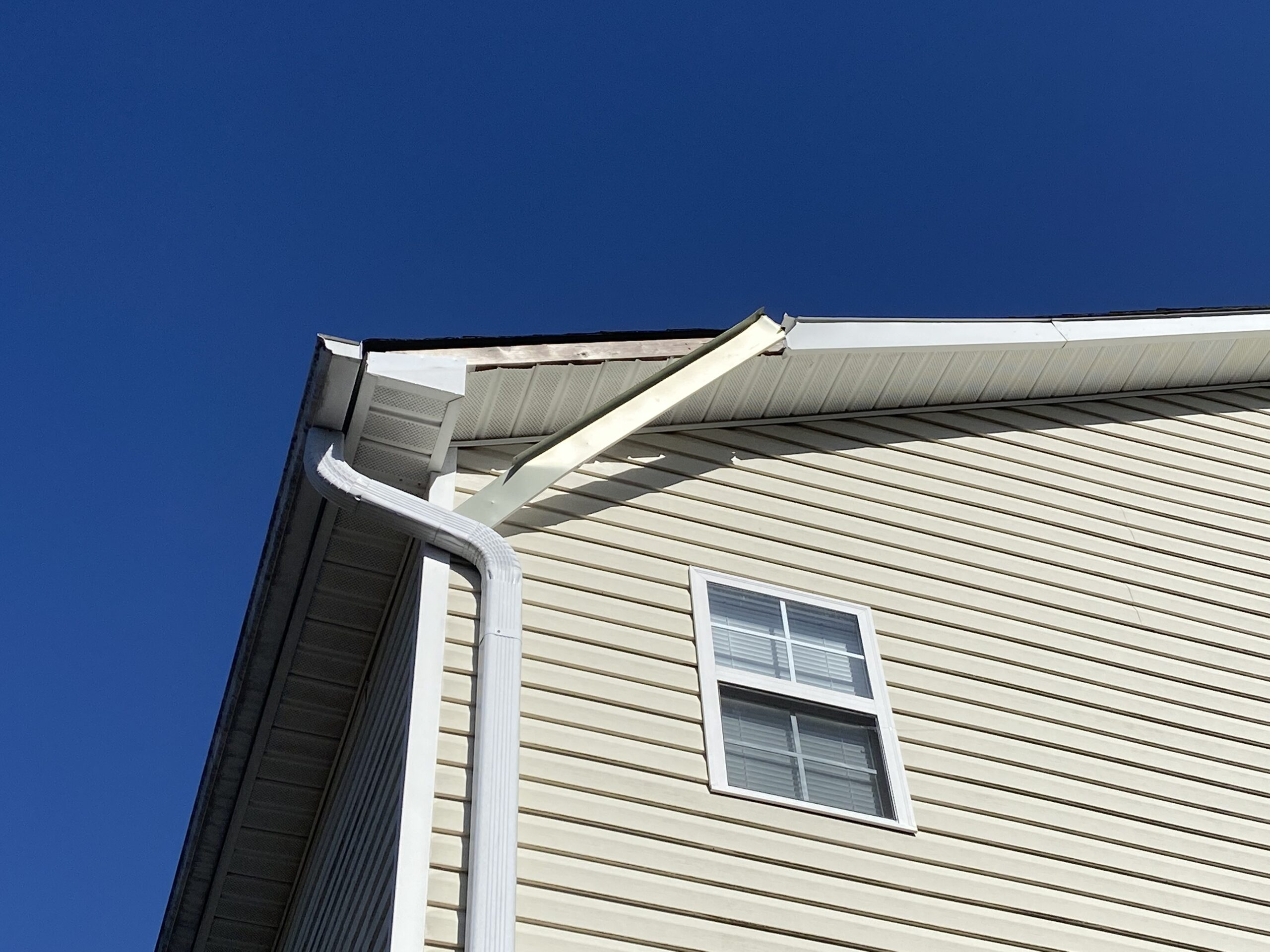 This is a picture of a two story home with white fascia metal that is falling down