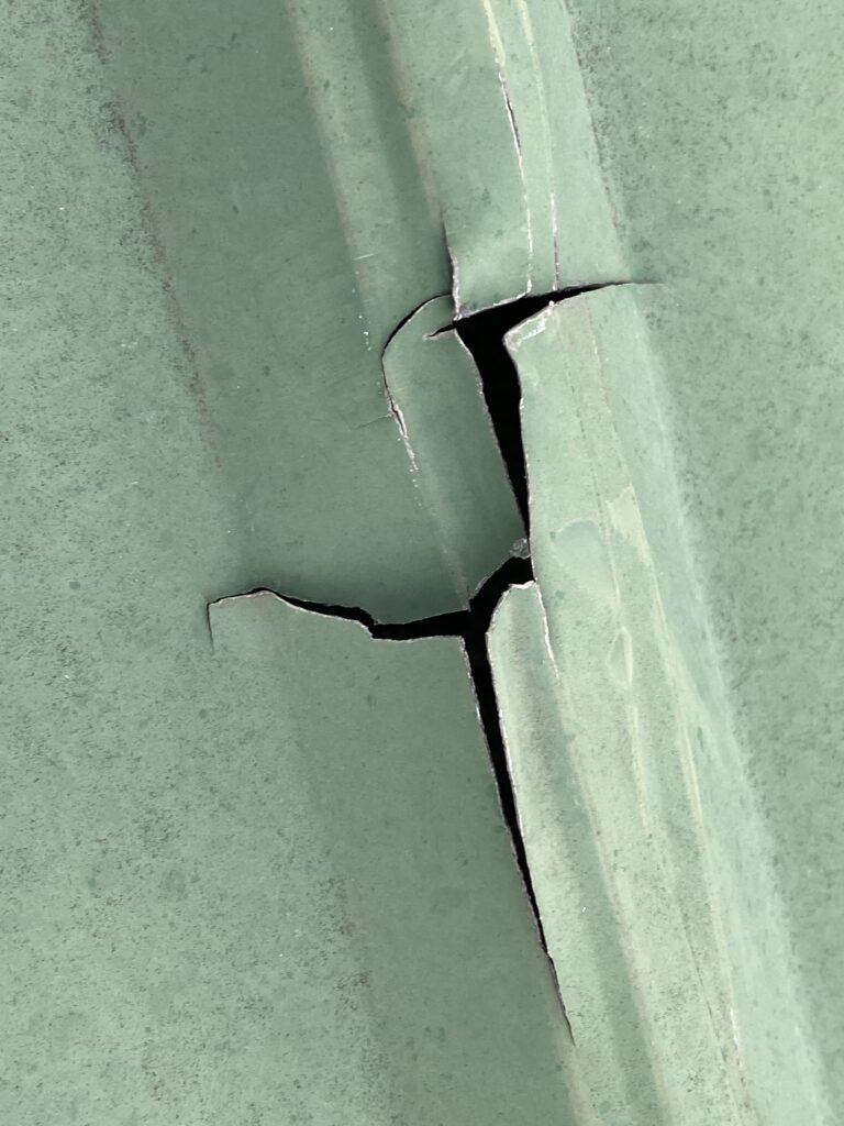 This is a view of a green metal roof panel with a large crack.