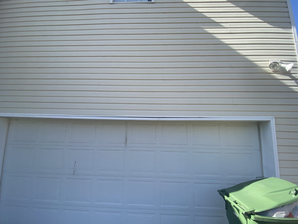 This is a picture of a white garage door with white trim that is falling