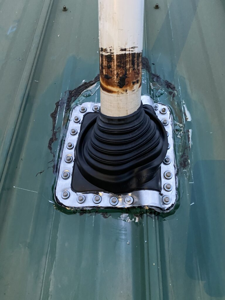This is a close up picture of a metal roof that has a new black rubber pipe boot that is installed on a plumbing vent.