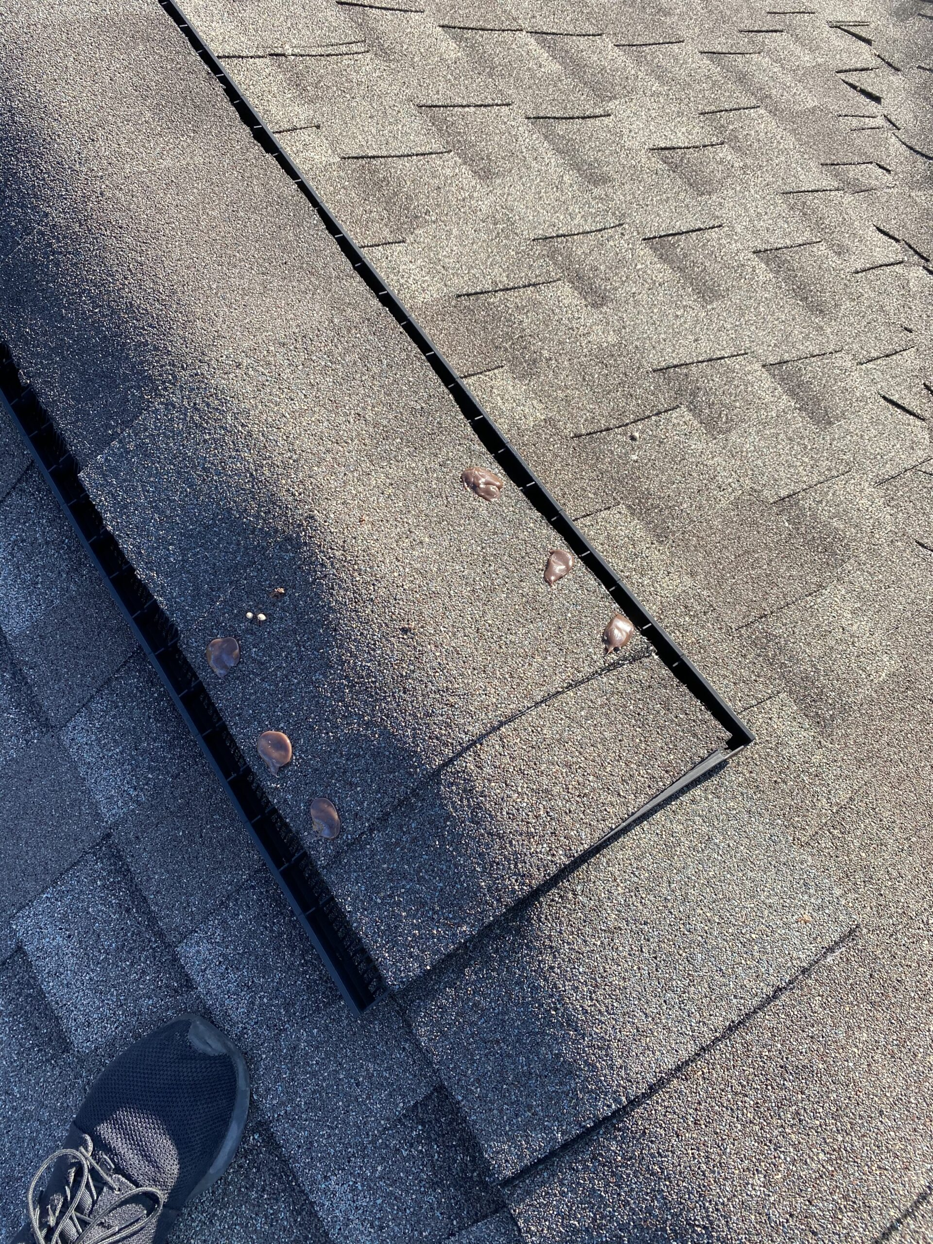 This is a picture of brown shingles on a ridge cap that has sealed nails