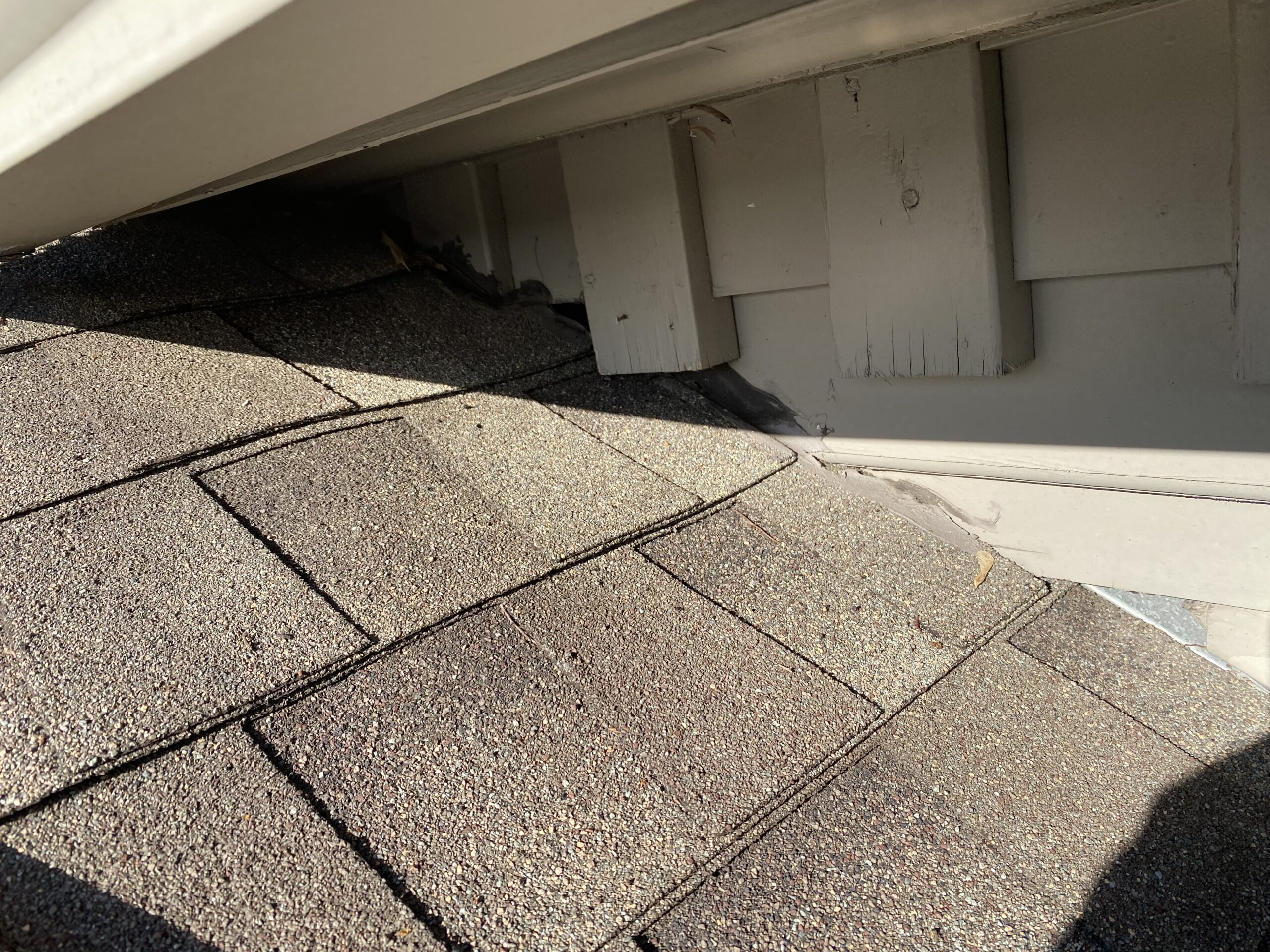 This is a picture of brown shingles below a wicker colored gutter