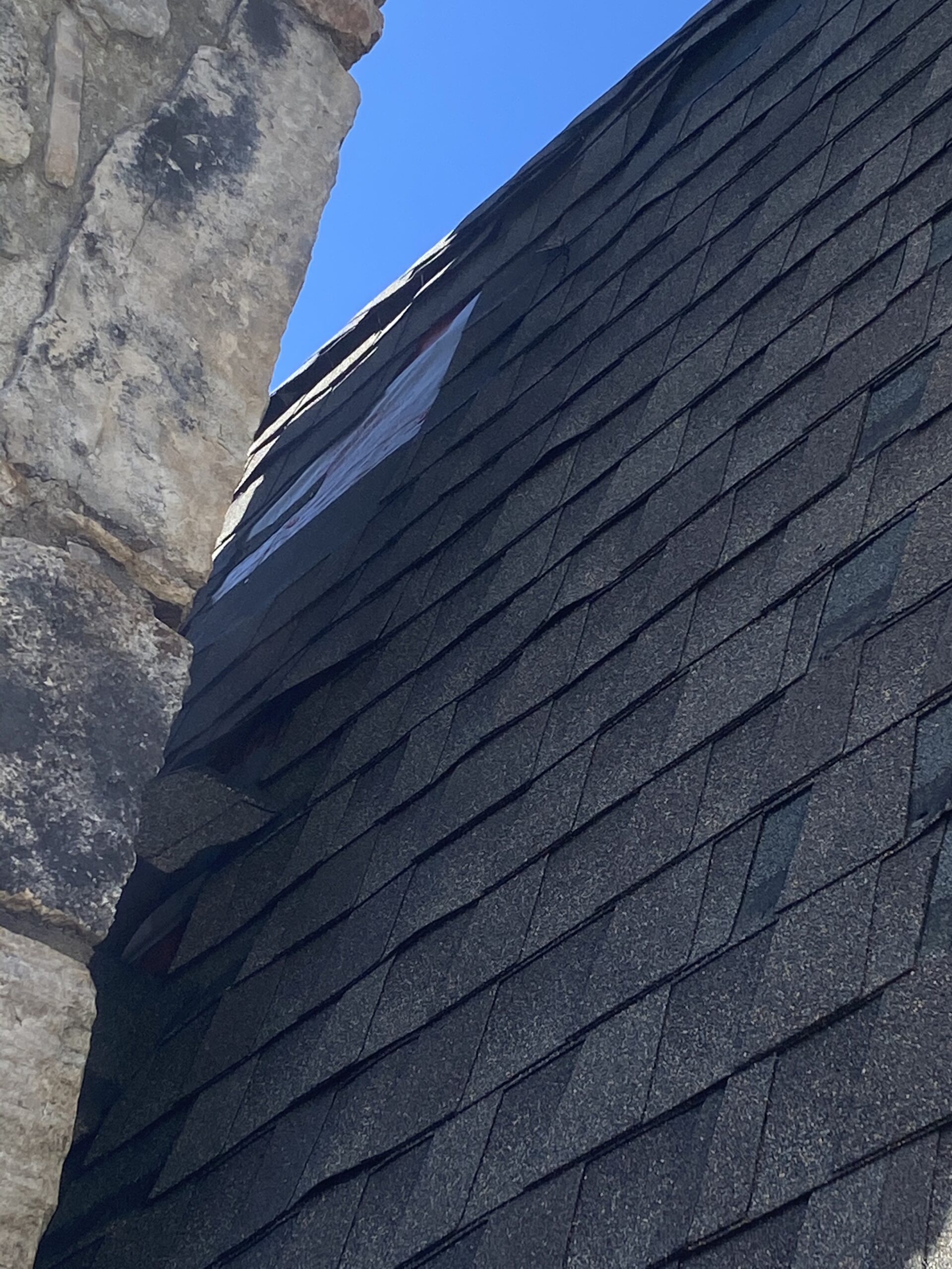 This is a picture of shingles missing behind the chimney