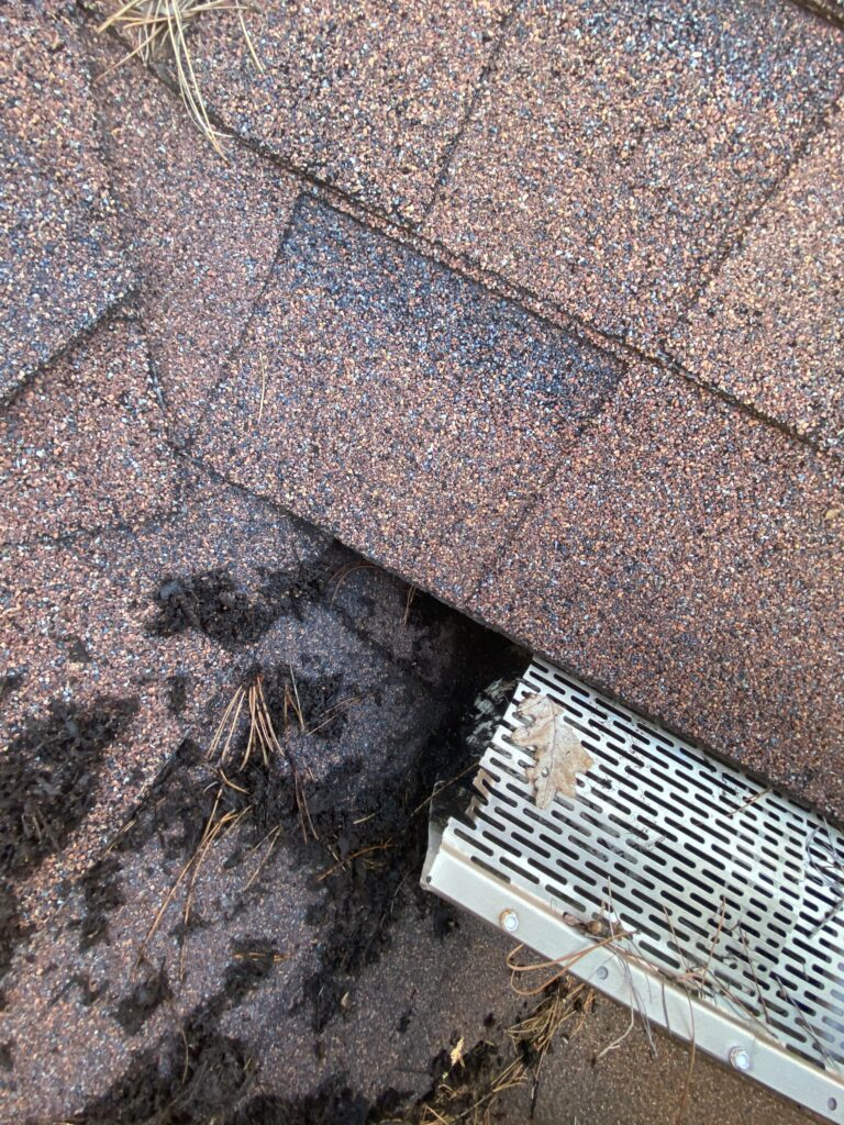 This is a picture of an almond color gutter that is butting up against the roof.