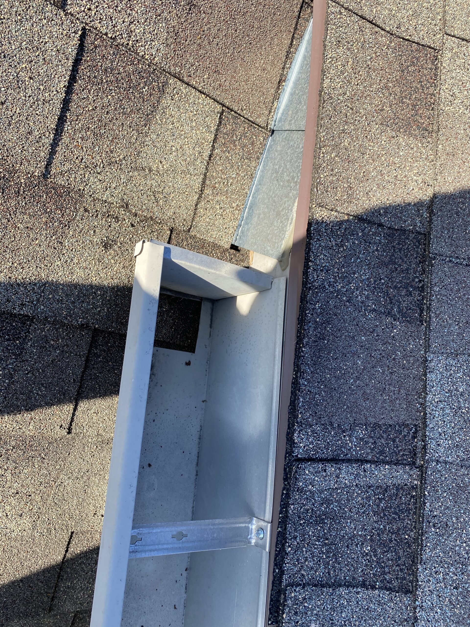 This is a picture of a wicker colored gutter with a hole in it and brow shingle roof.