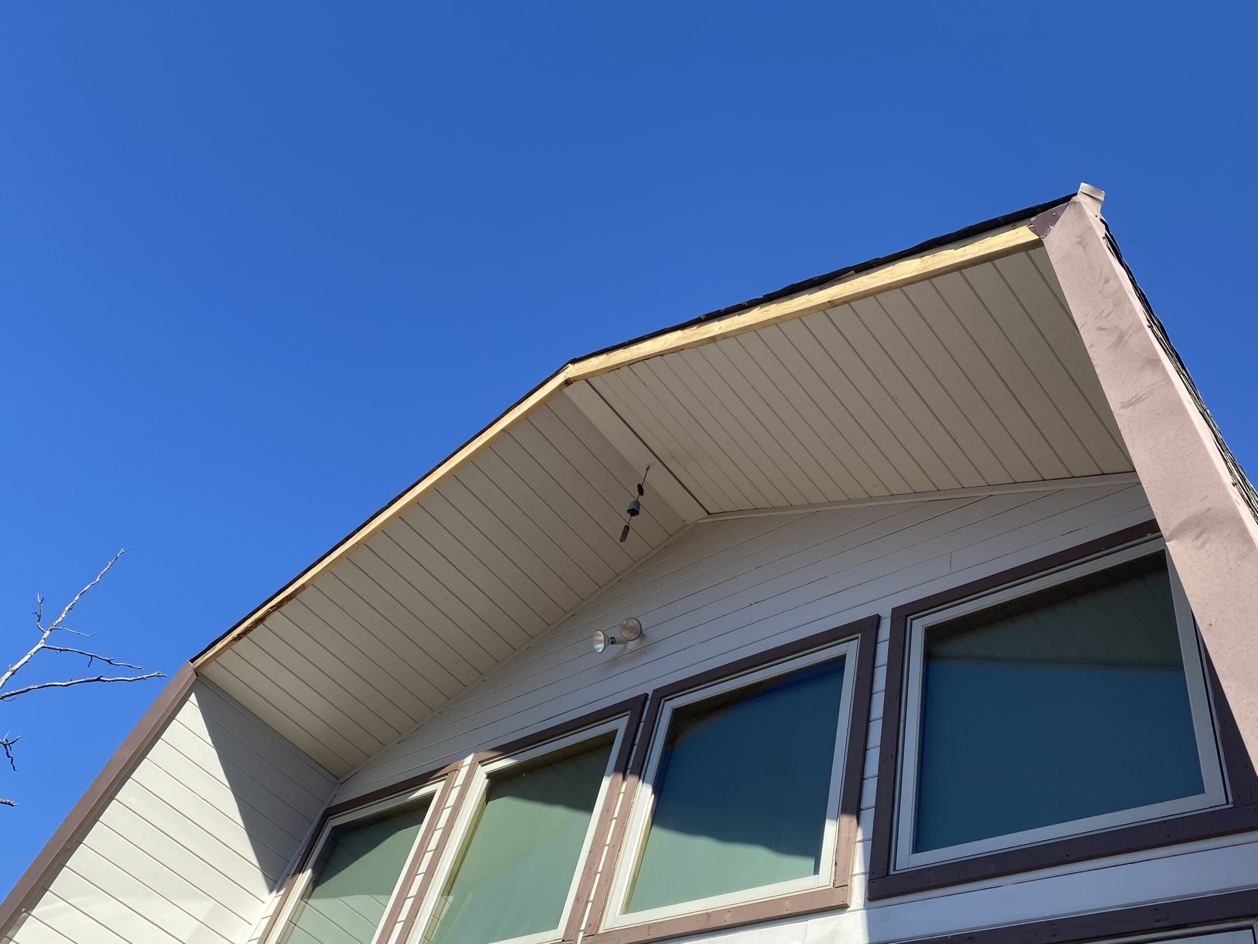 This is a picture of an A frame house that has fascia metal missing
