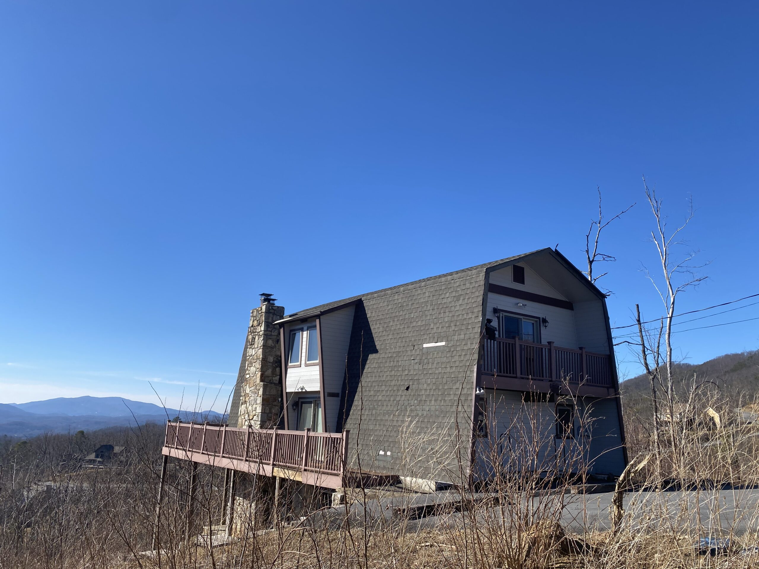 This is a picture of an A frame house on top of a mountain needing a new roof