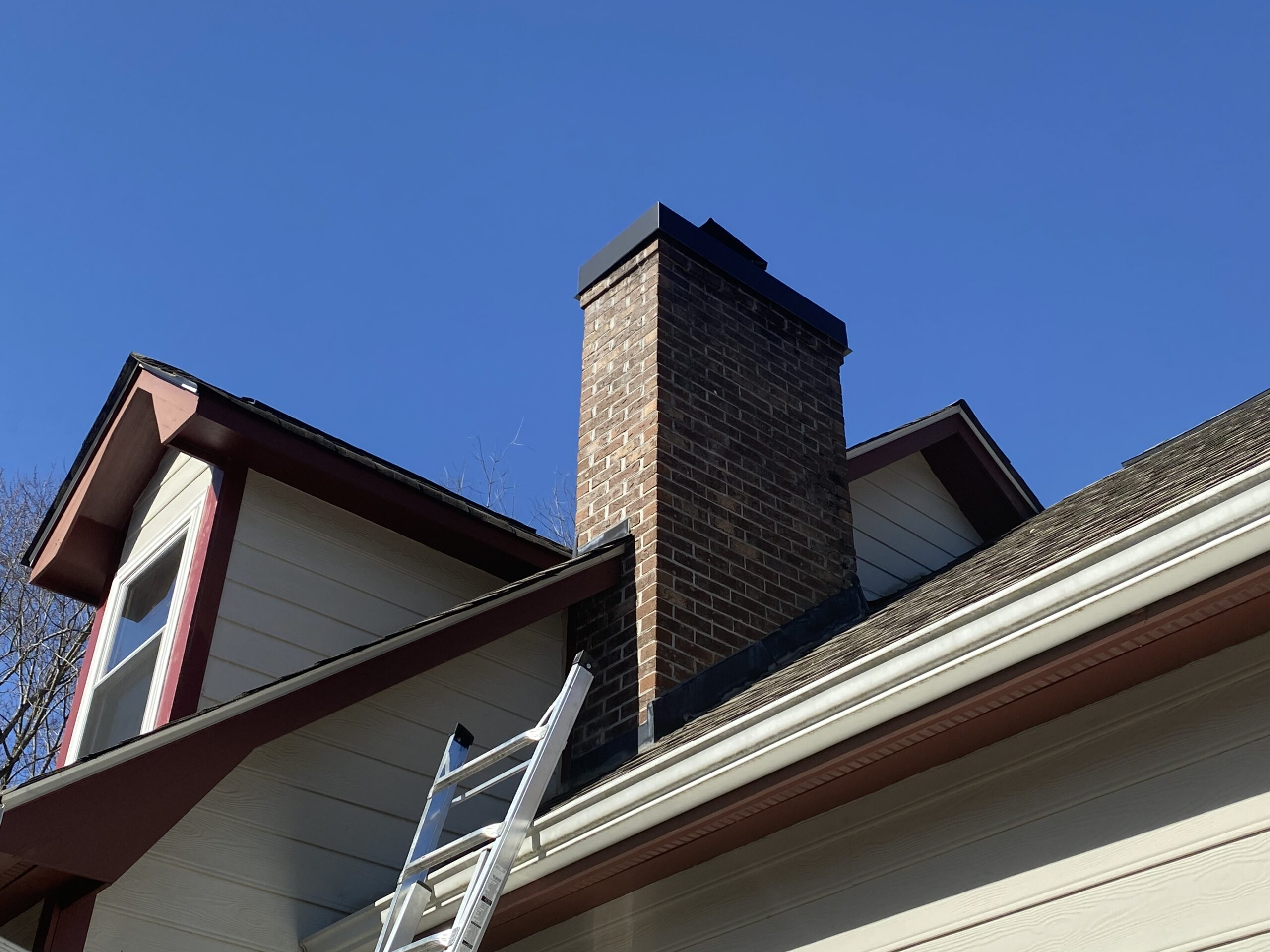 This is a picture of a white and red home with a brick chimney