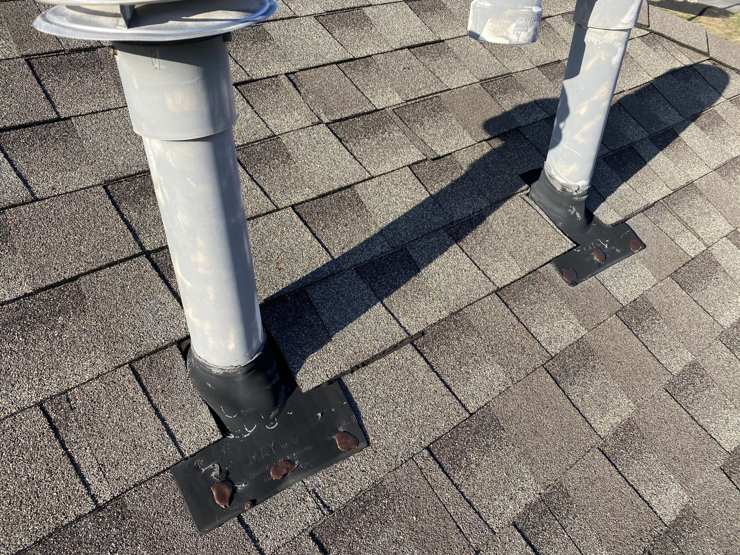 This is a picture of pipe boots on a brown roof that were sealed with caulk.