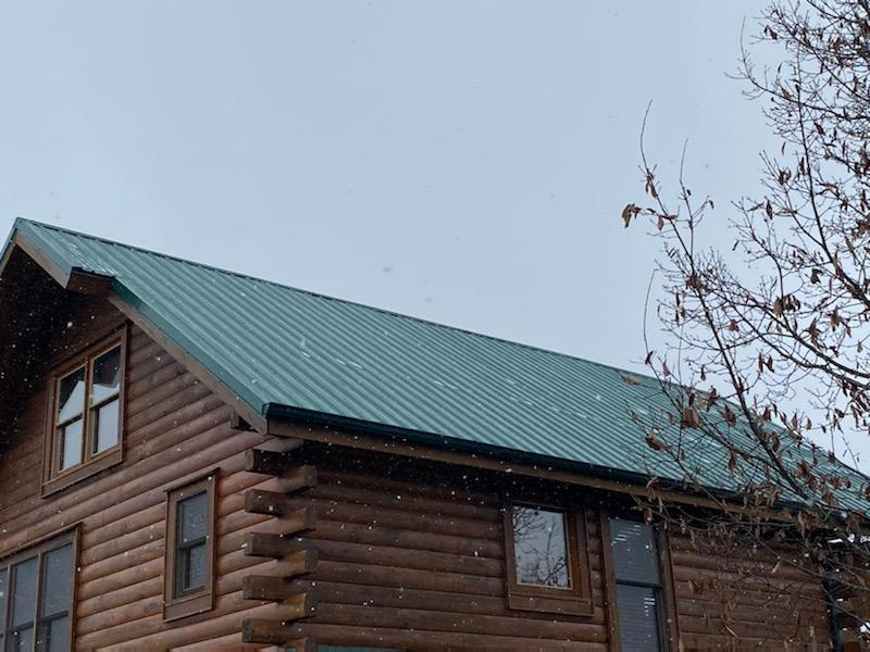 This is a picture of a log cabin with a brand new green metal roof sitting on top of a hill in the middle of the mountains.