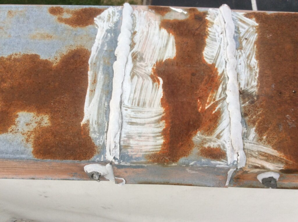 This is a view of rusted metal with white caulk to seal the laps.