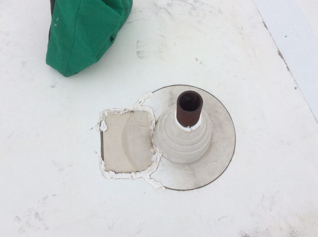 This is a view of a patch near a gas vent on a white TPO flat roof.