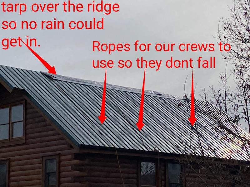 This is a picture of a green metal roof that was just installed on a cabin up in the mountains and there is ropes on the roof to tie off to.