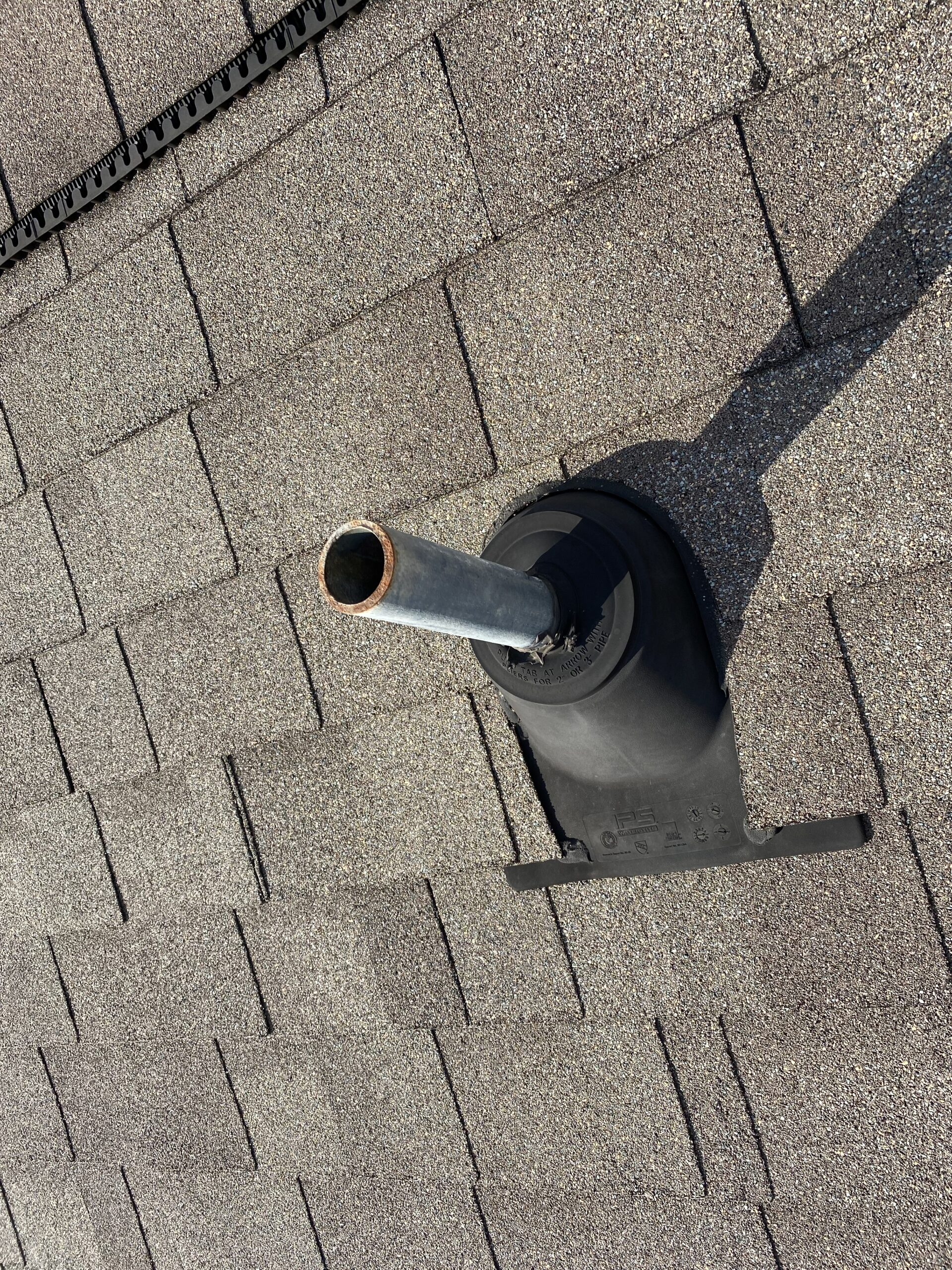 This is a picture of a brown roof with a pipe boot that needs some work