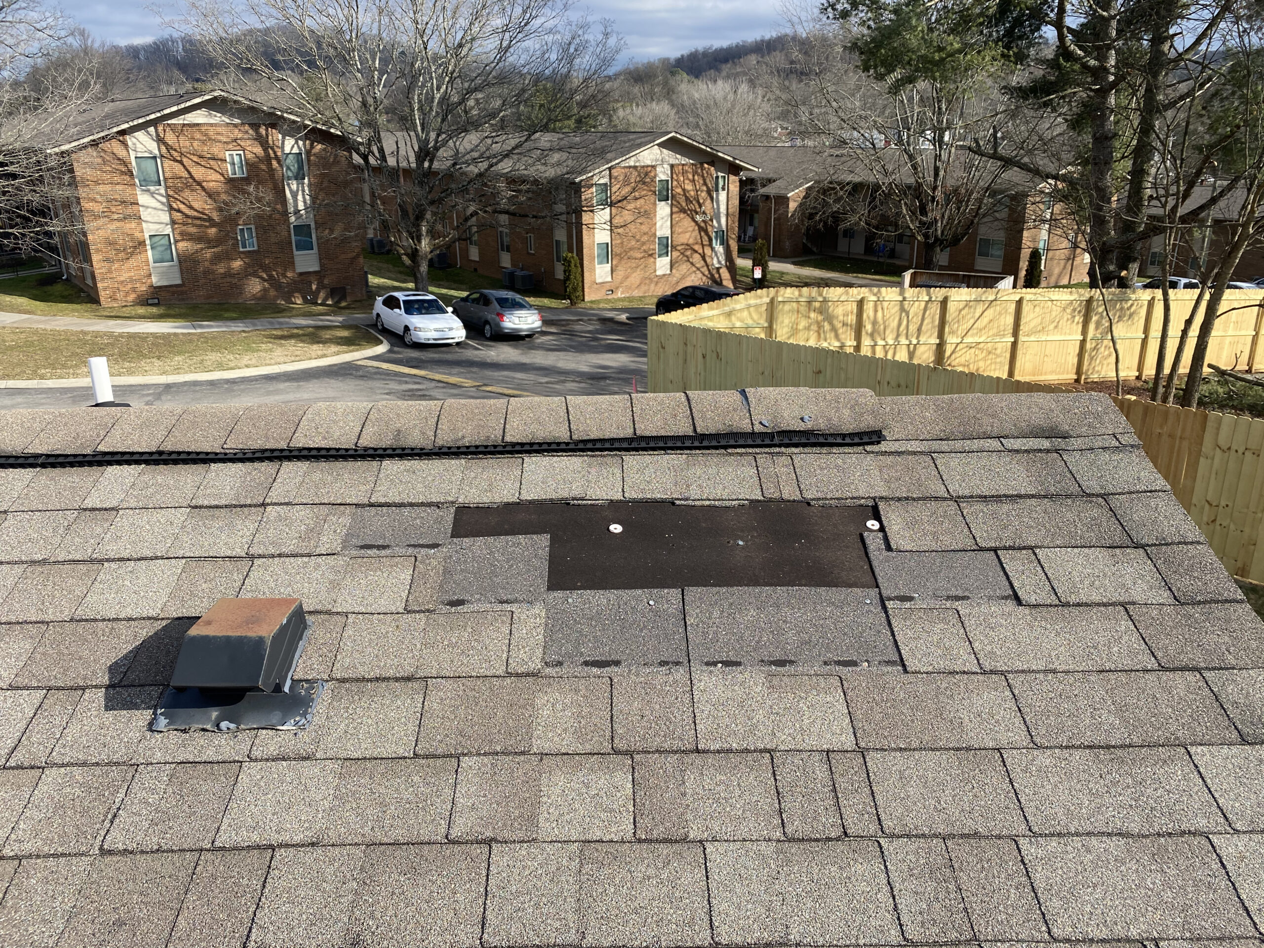 This is a picture of a brown roof that is missing about four shingles at the ridge.