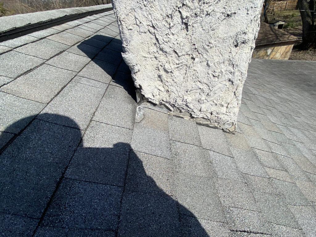 This is a picture of a white chimney needing new flashing