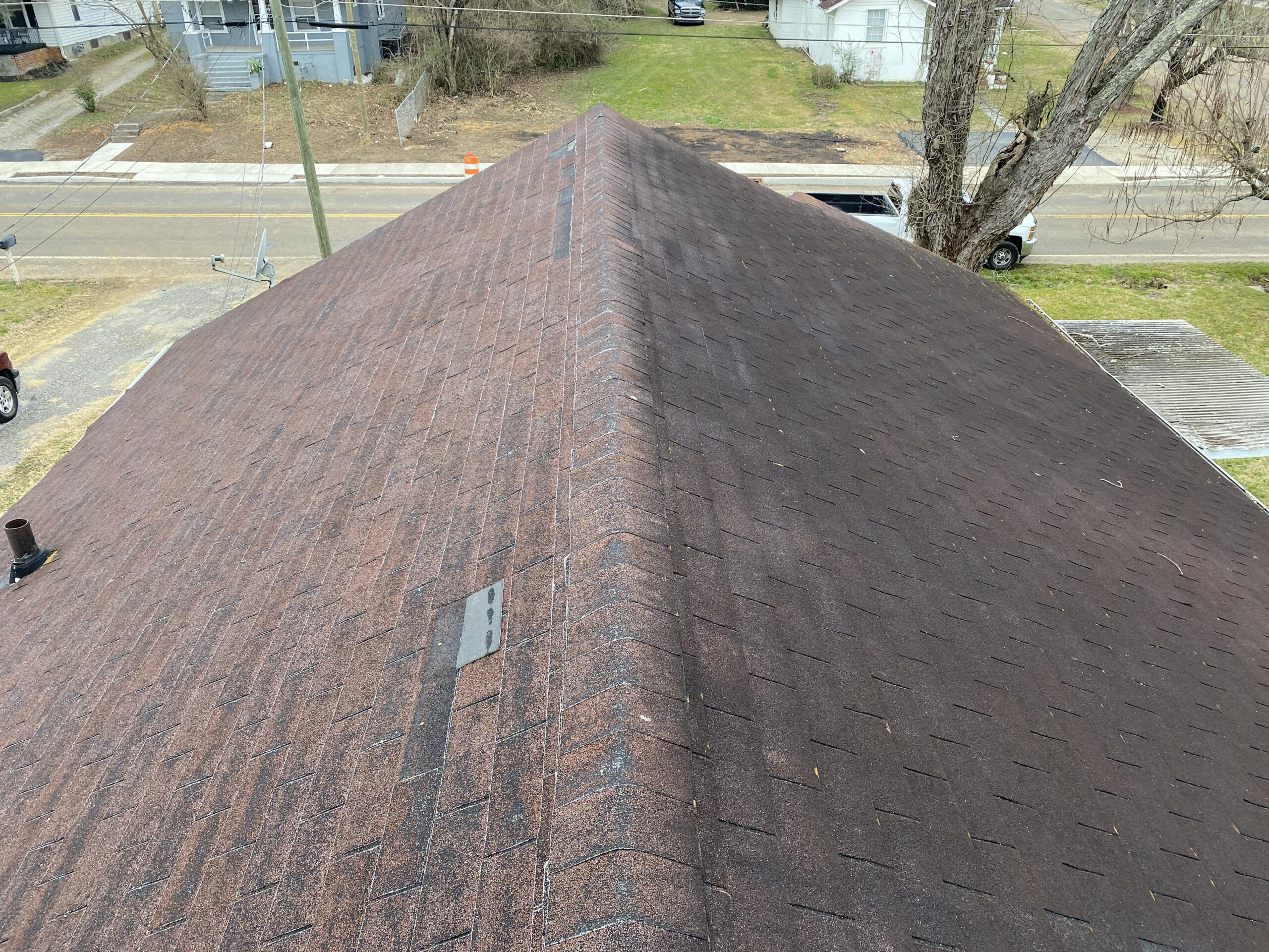 This is a picture of an old brown roof with missing shingles