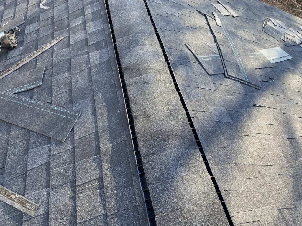 This is a picture of a ridge vent with charcoal black shingles