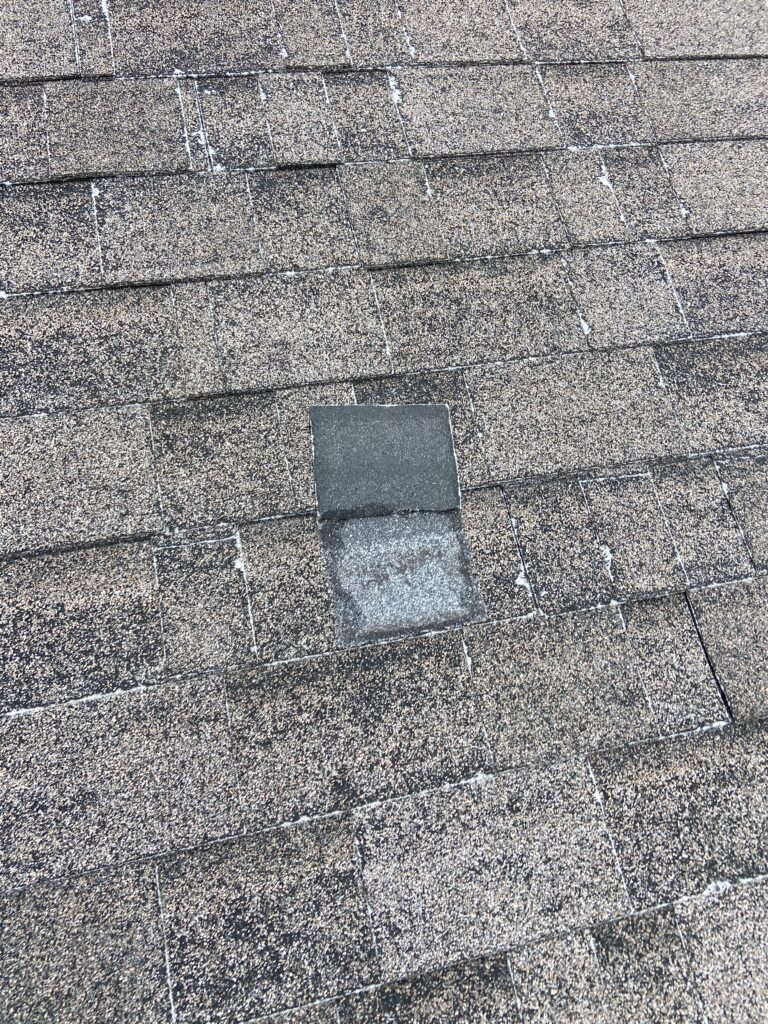 This is a picture of a gray shingle that is old with storm damage