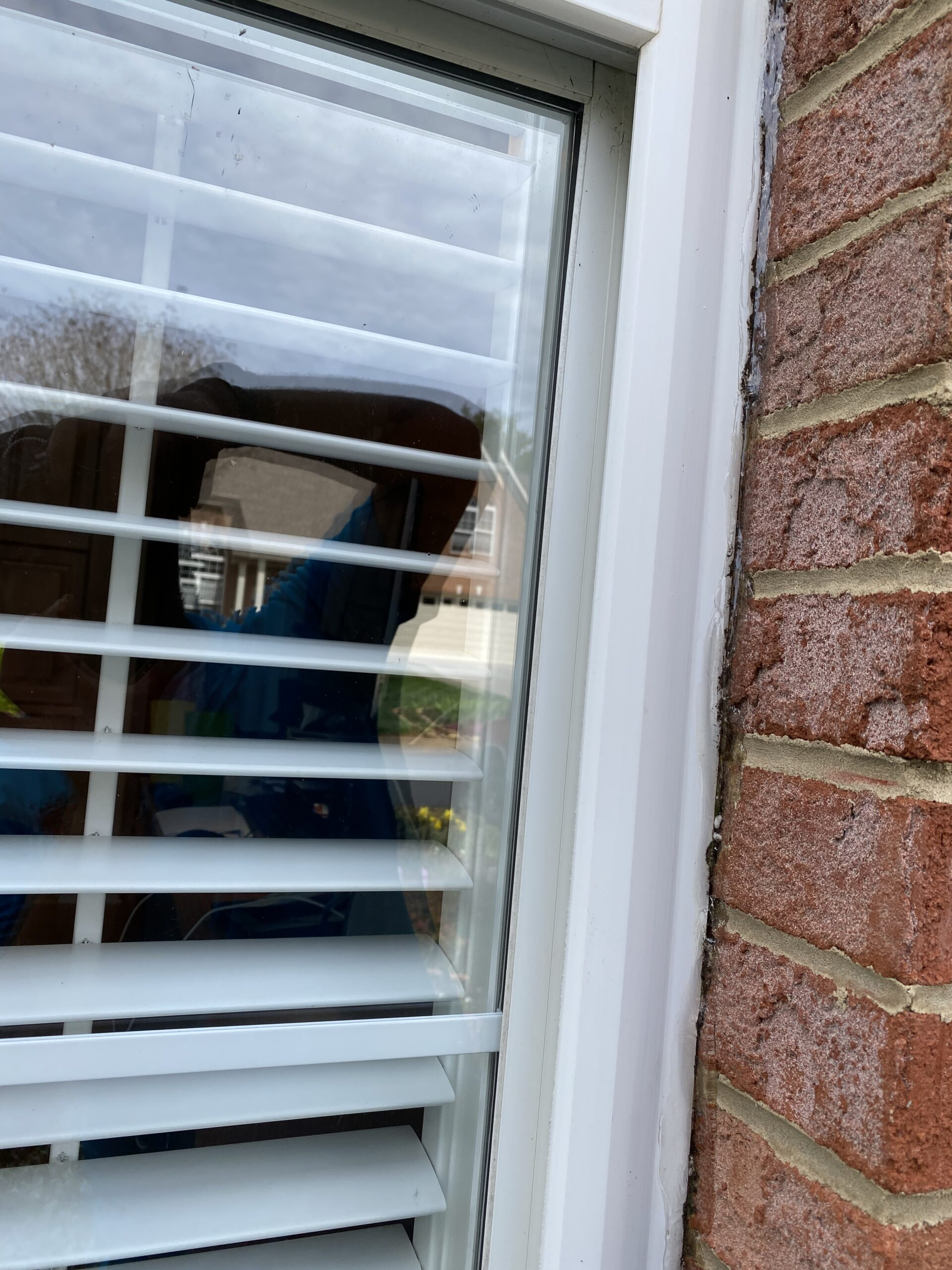 This is a picture of a window at a brick wall that has been sealed with clear caulk