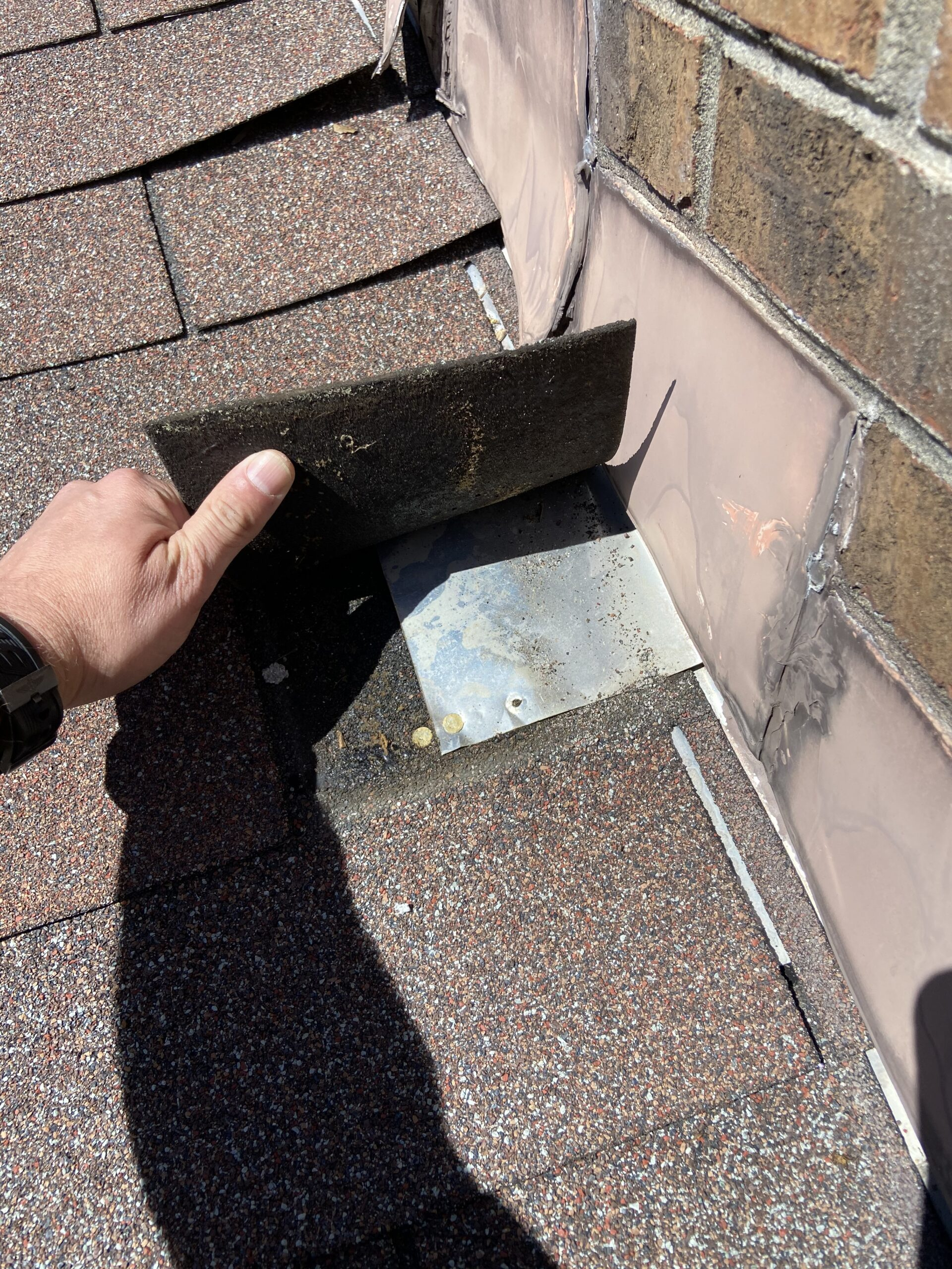 This is a picture of chimney step flashing that is improperly Nailed