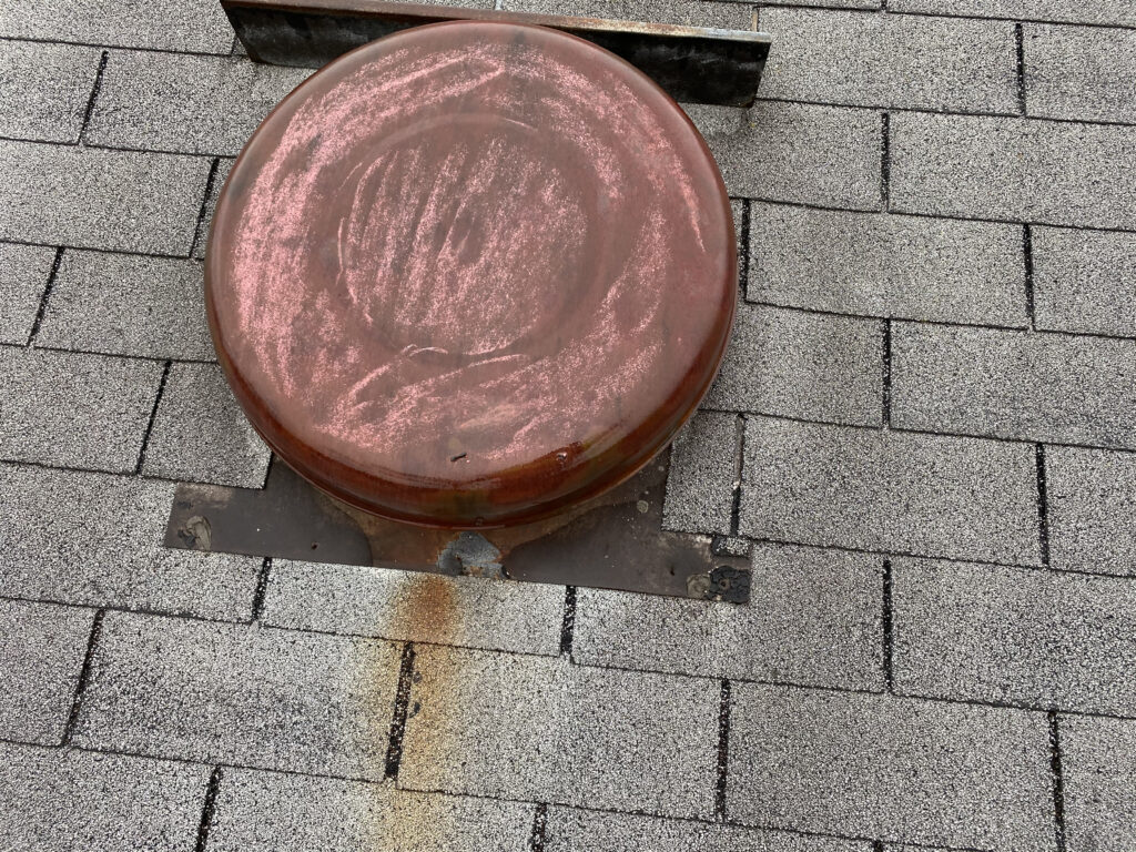 This is a picture of an old red roof vent