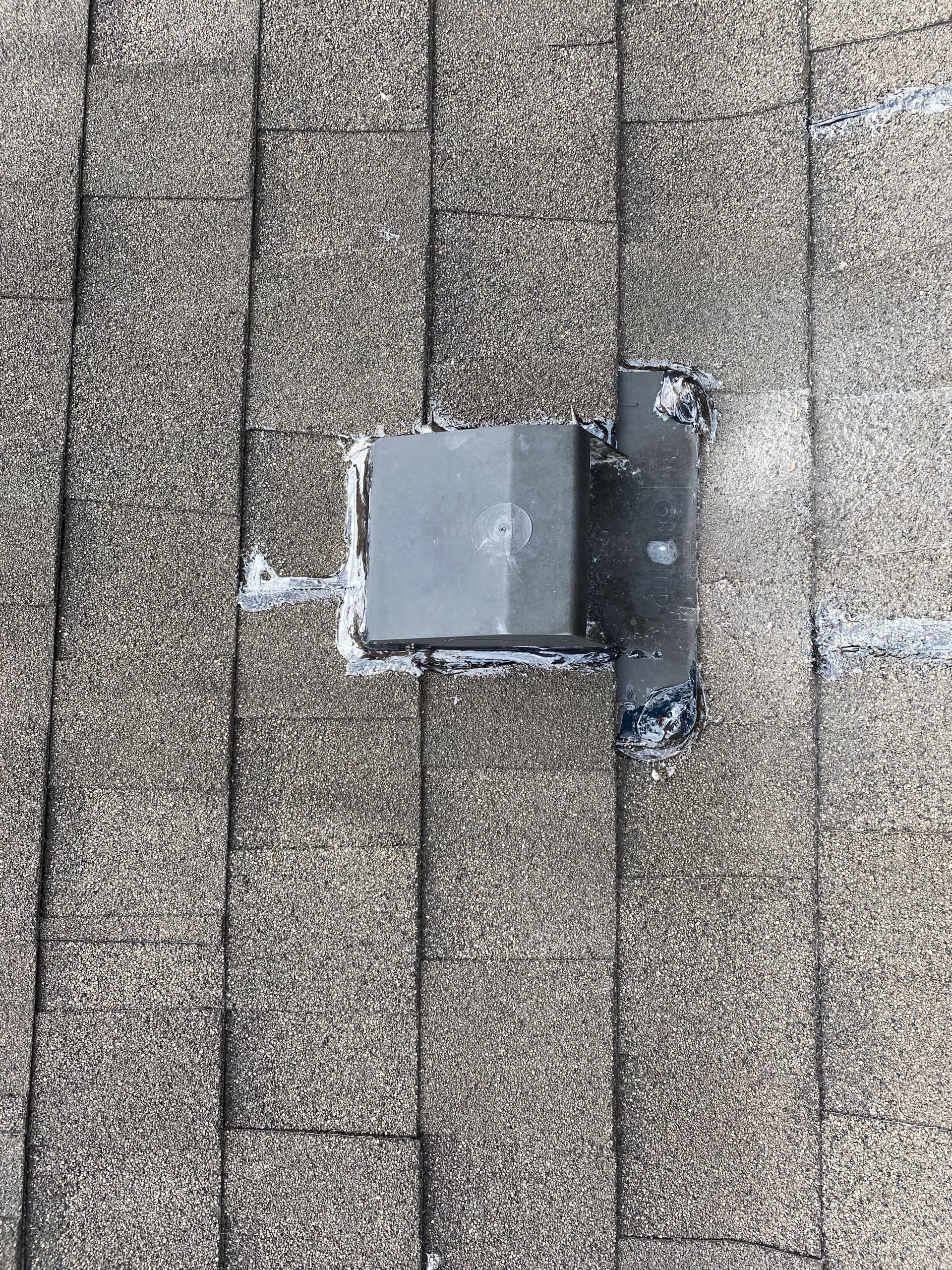 This is a picture of a black exhaust vent that has been sealed with clear caulk