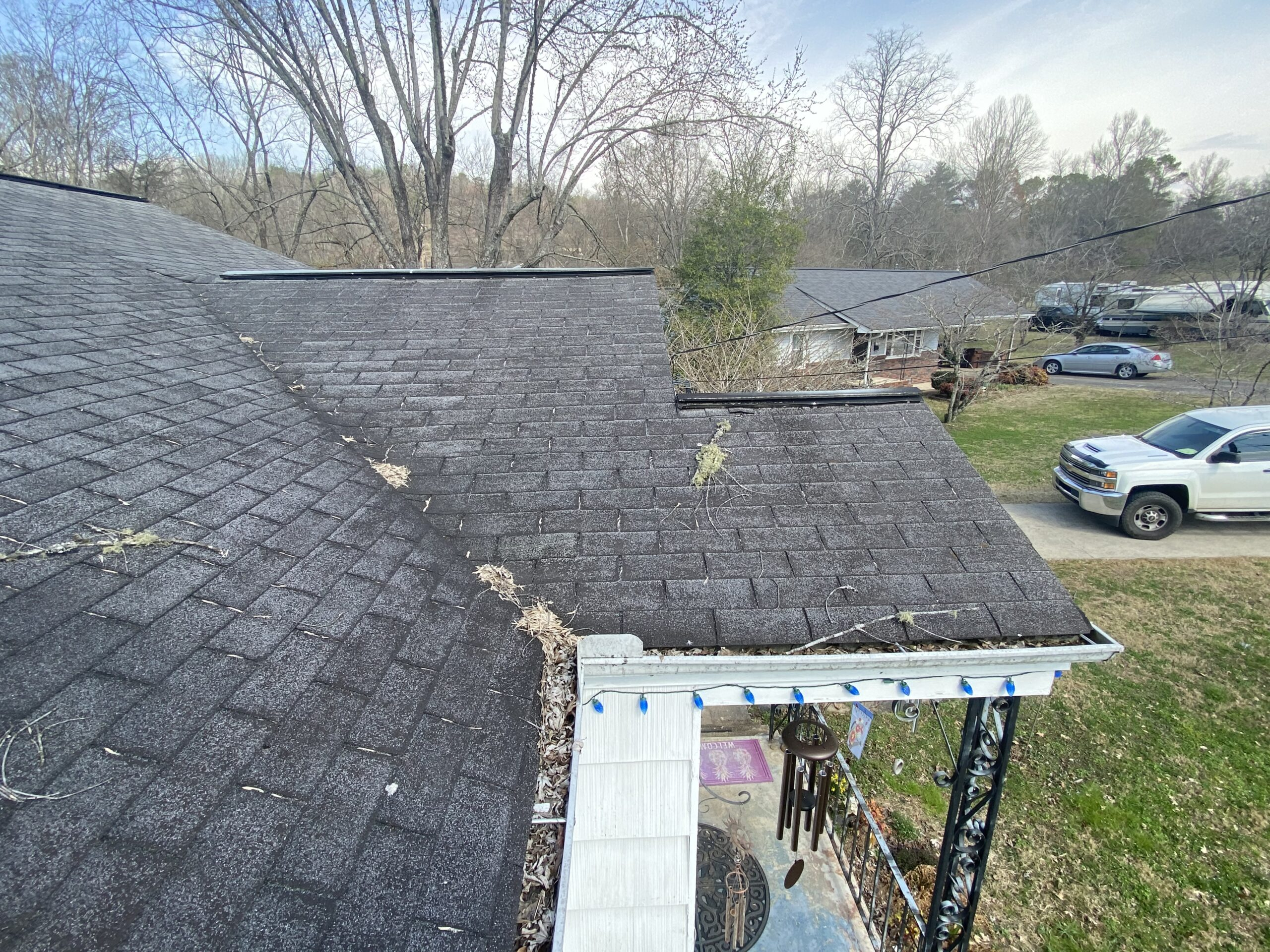 This is a picture of a black roof with gutters full of leaves.