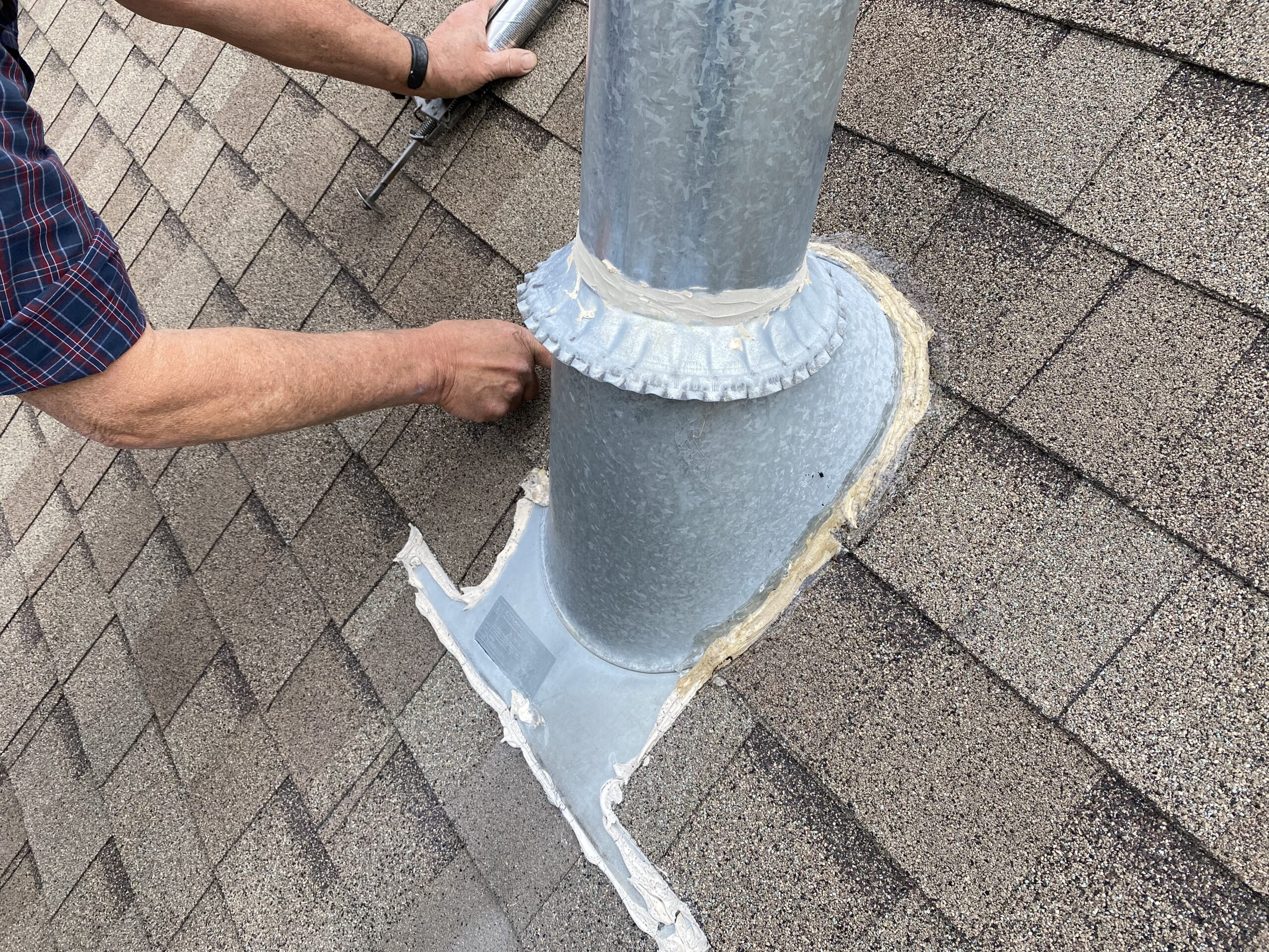 This is a picture of a silver exhaust stack that has been sealed with clear caulk