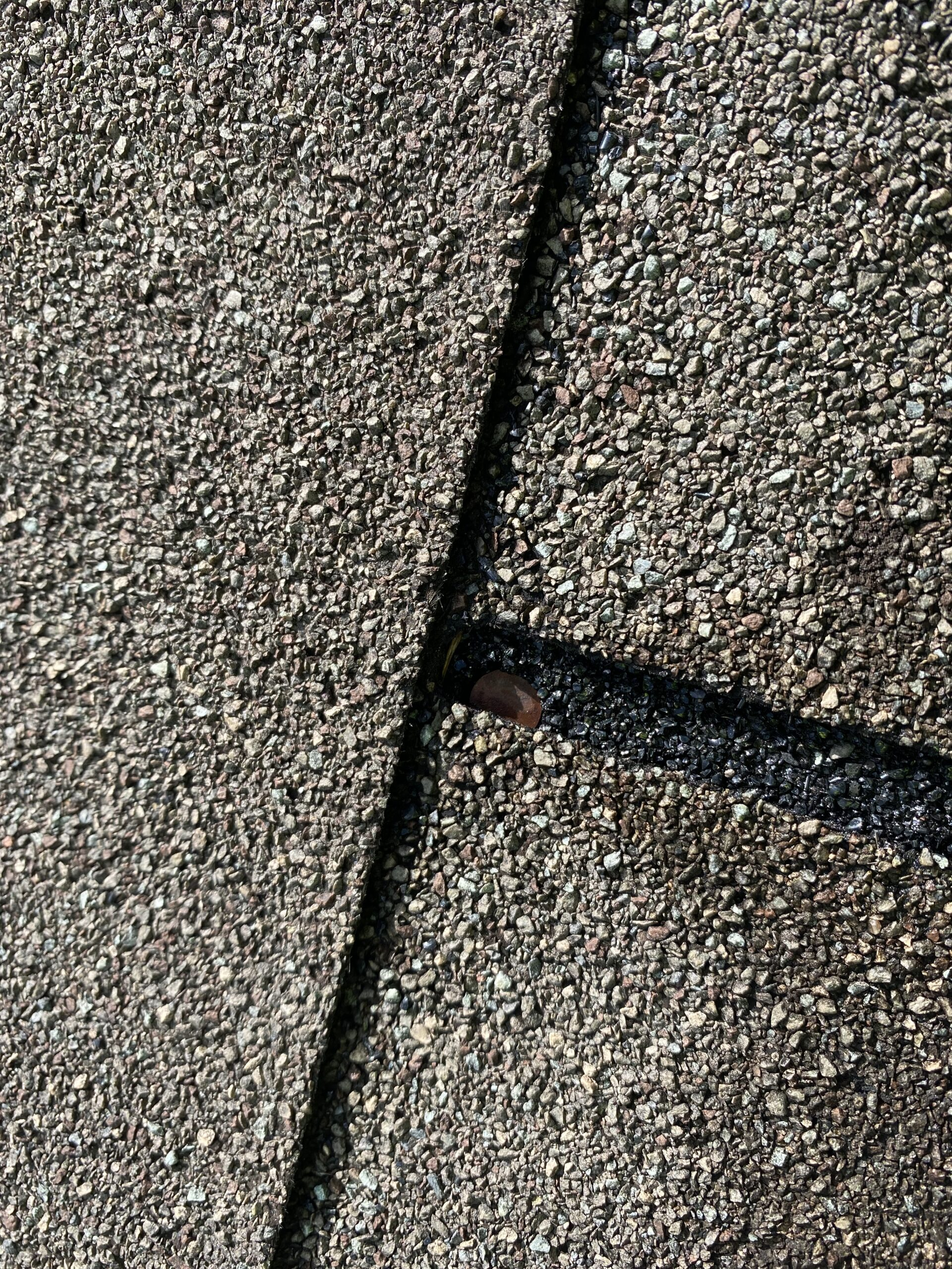 This is a picture of an exposed nail at the union of a shingle