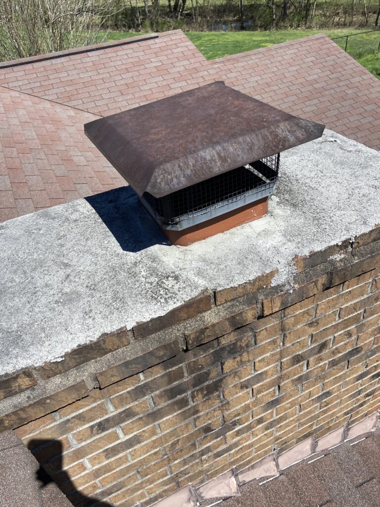 This chimney can be leaking because the cap has cracks in it