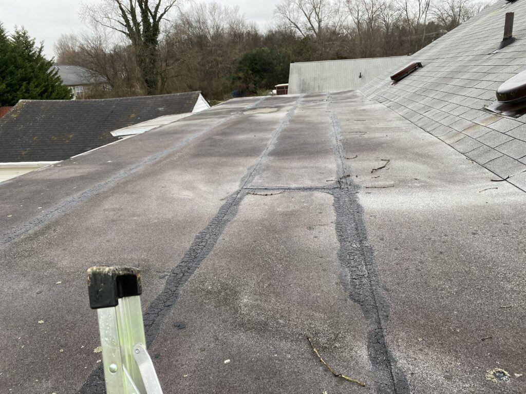 This is a picture of an old gray flat roof that needs TPO