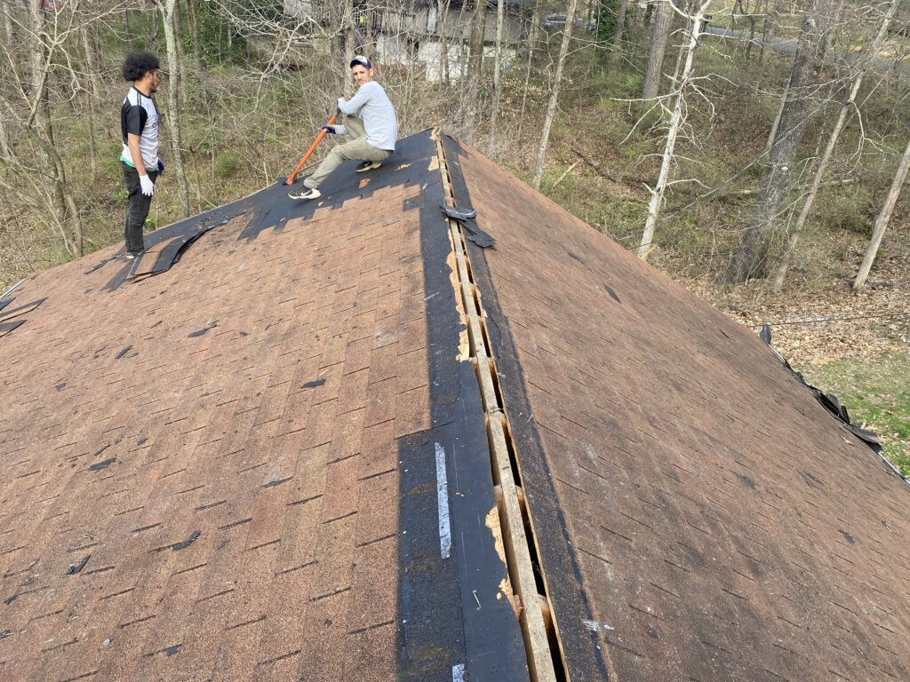 This is a picture of brown shingles on a ridge that is being torn off