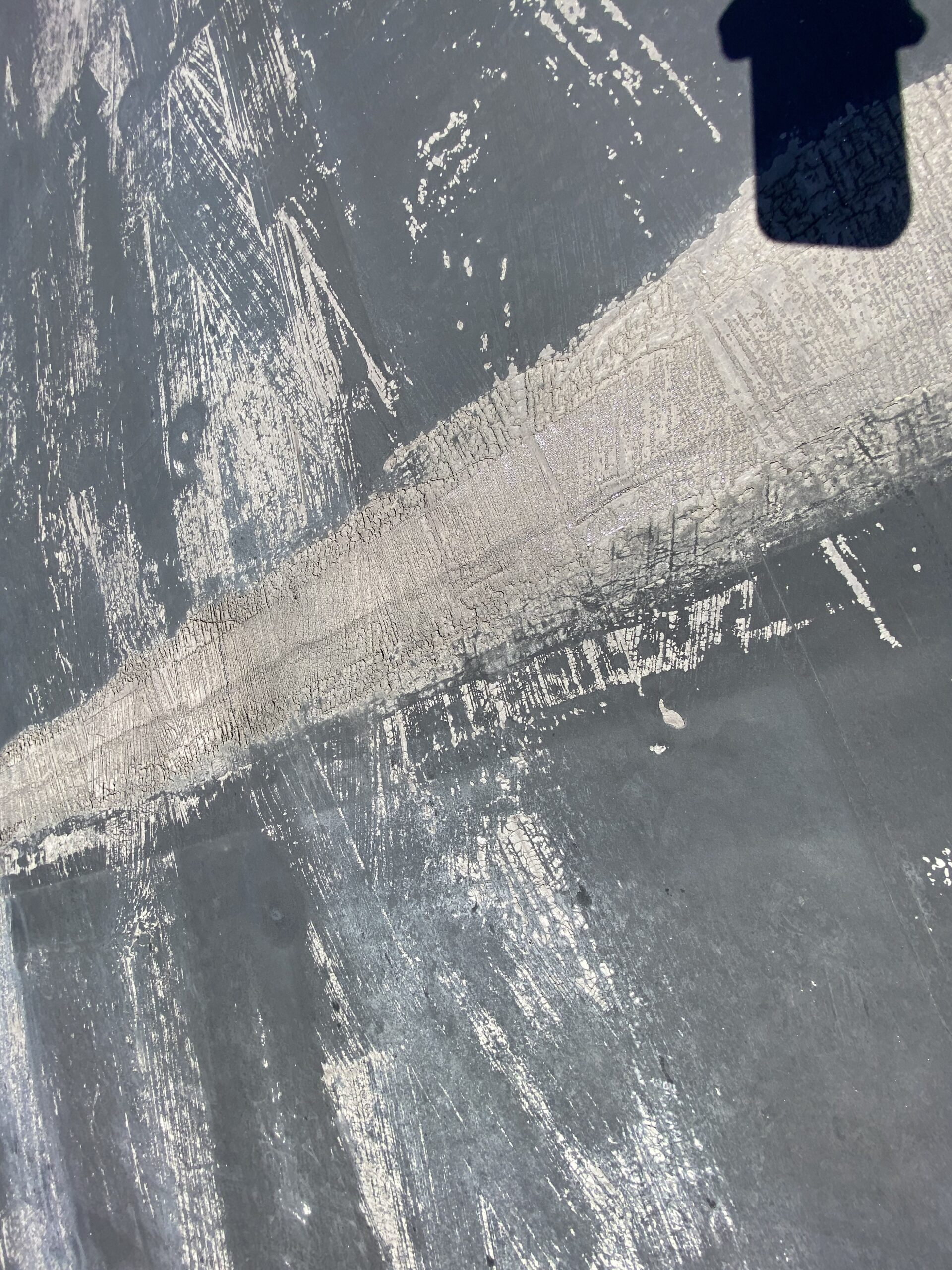 This is a picture of a seam that is cracked on an old black flat roof