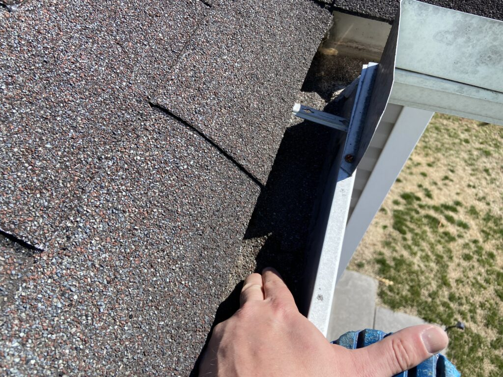 This is a picture of a gray shingle that is missing granules in the granular's are in the gutters of the roof