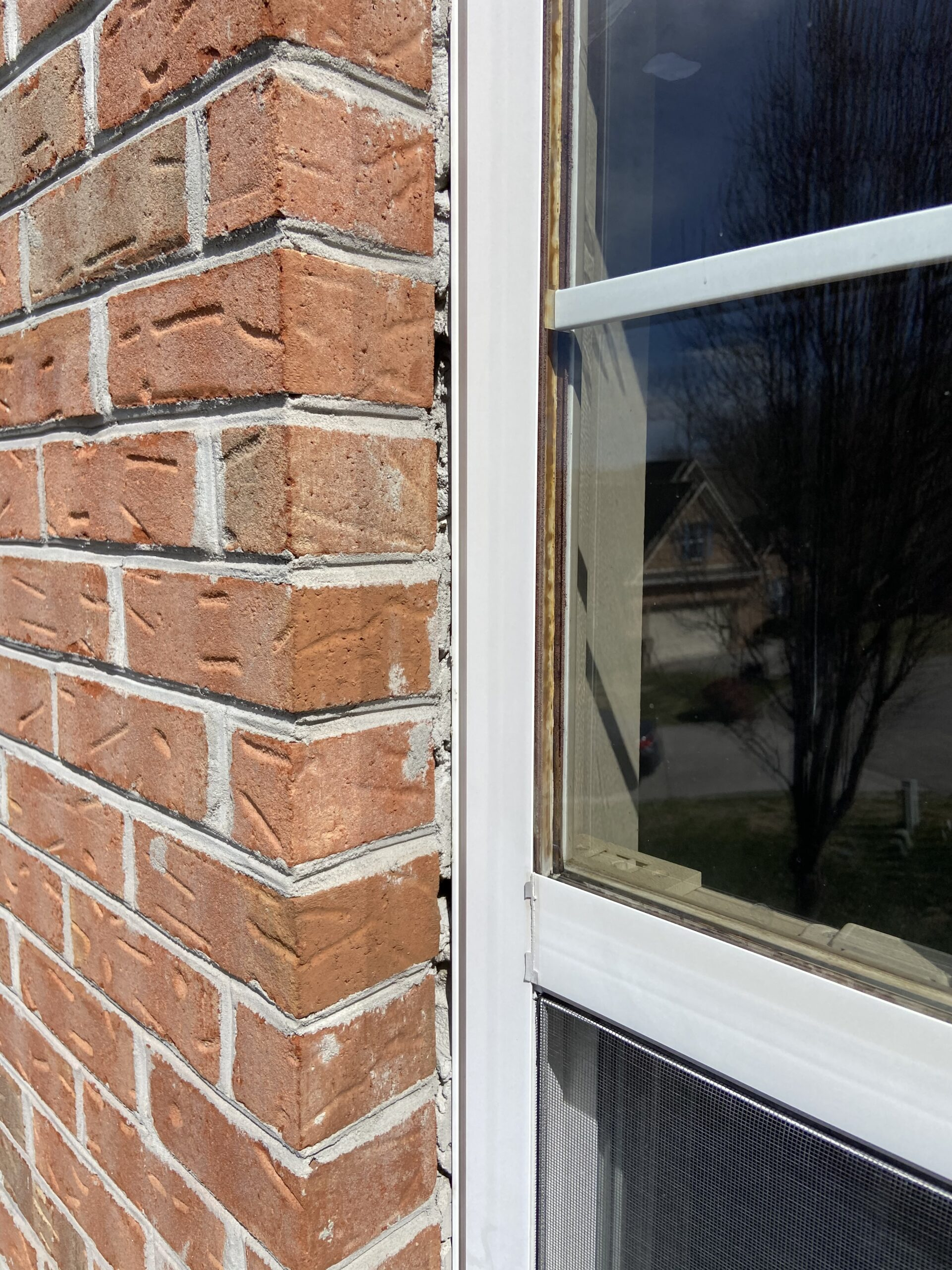 Huge gaps between brick siding and a vinyl window