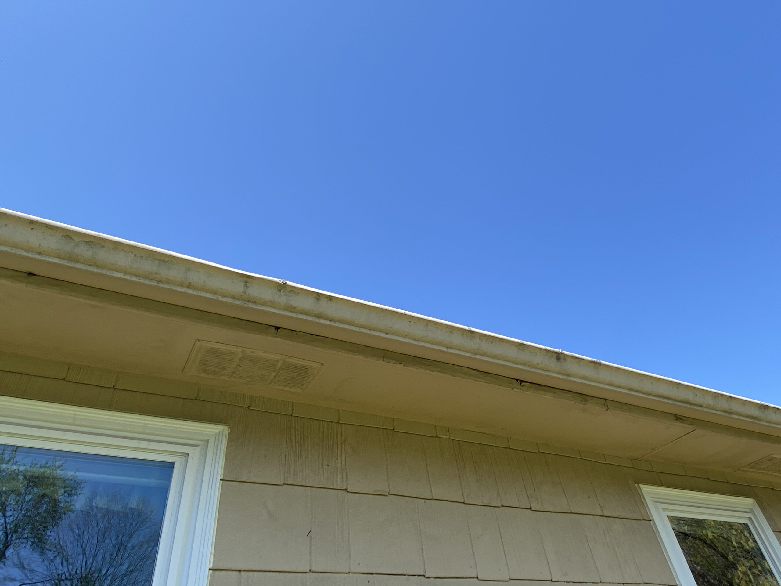 This is a picture of an old tan colored gutter