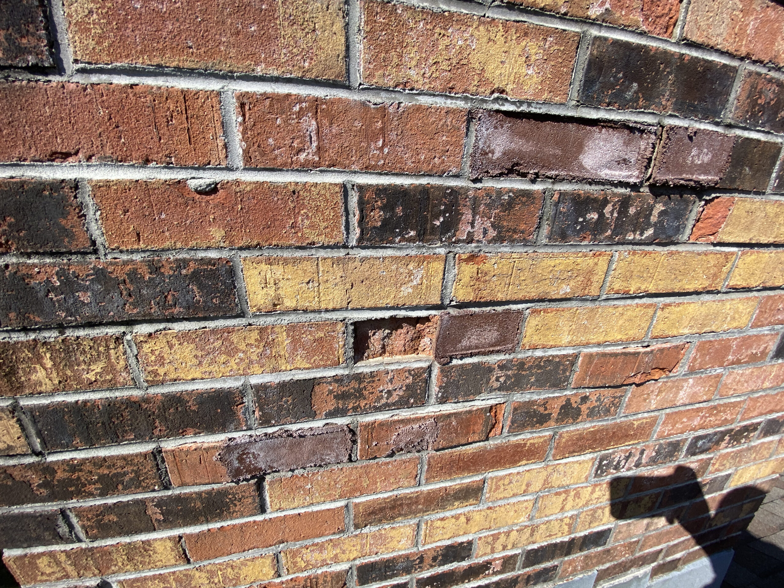 This is a picture of a brick chimney with cracks in the brick