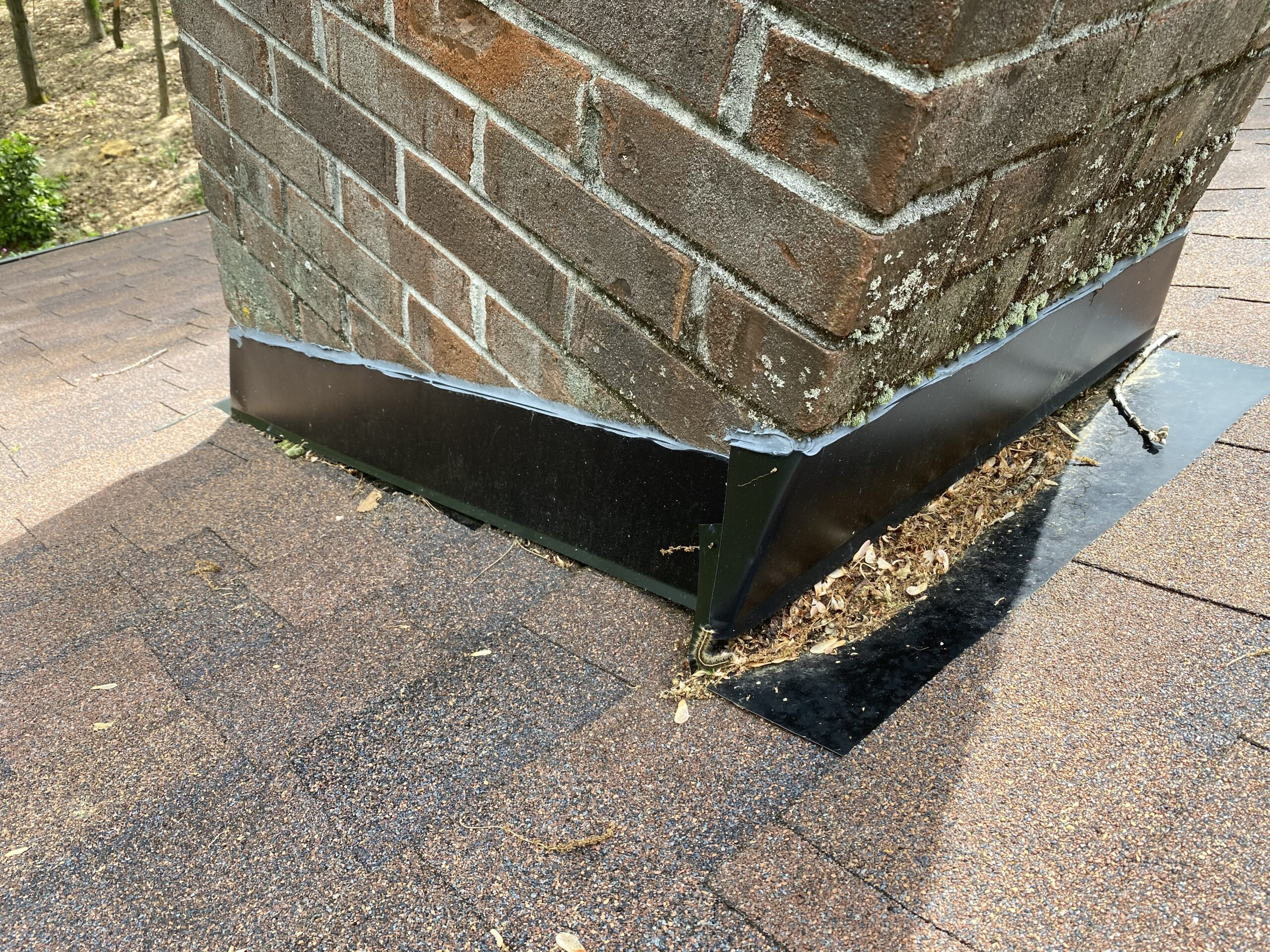 This is a picture elf black chimney flashing on a brick chimney