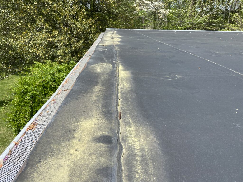 This is a picture of the edge of a rubber roof that has water that collects stands and leaks on it