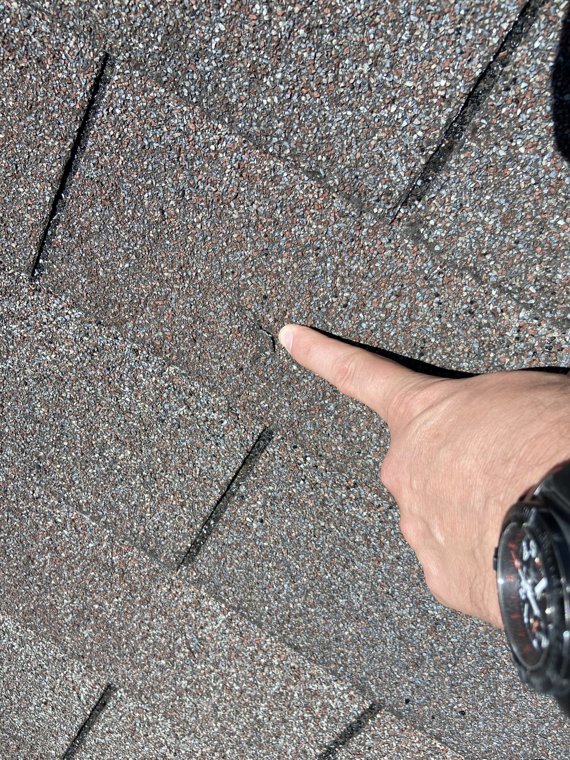 This is a picture of a gray roof with a hole in it and I'm pointing out the hole